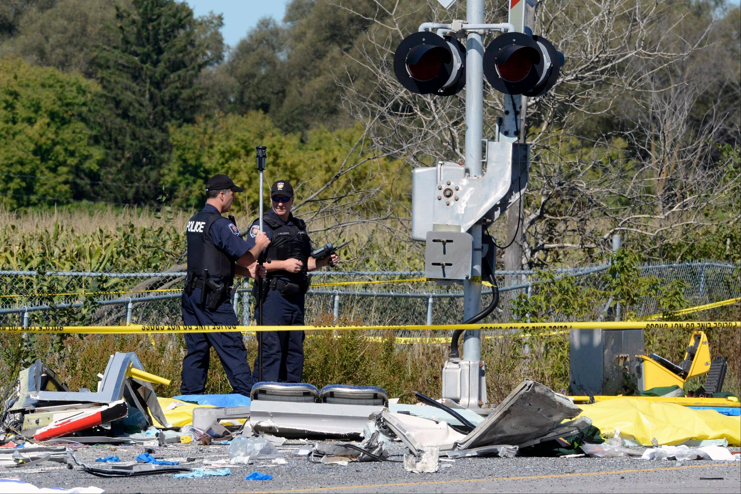 Police officers monitor the scene of a collision with a train and a city bus in Ottawa, Ontario, Wednesday, Sept. 18, 2013. An Ottawa Fire spokesman said there are ìmultiple fatalitiesî and a number of people injured from the bus.