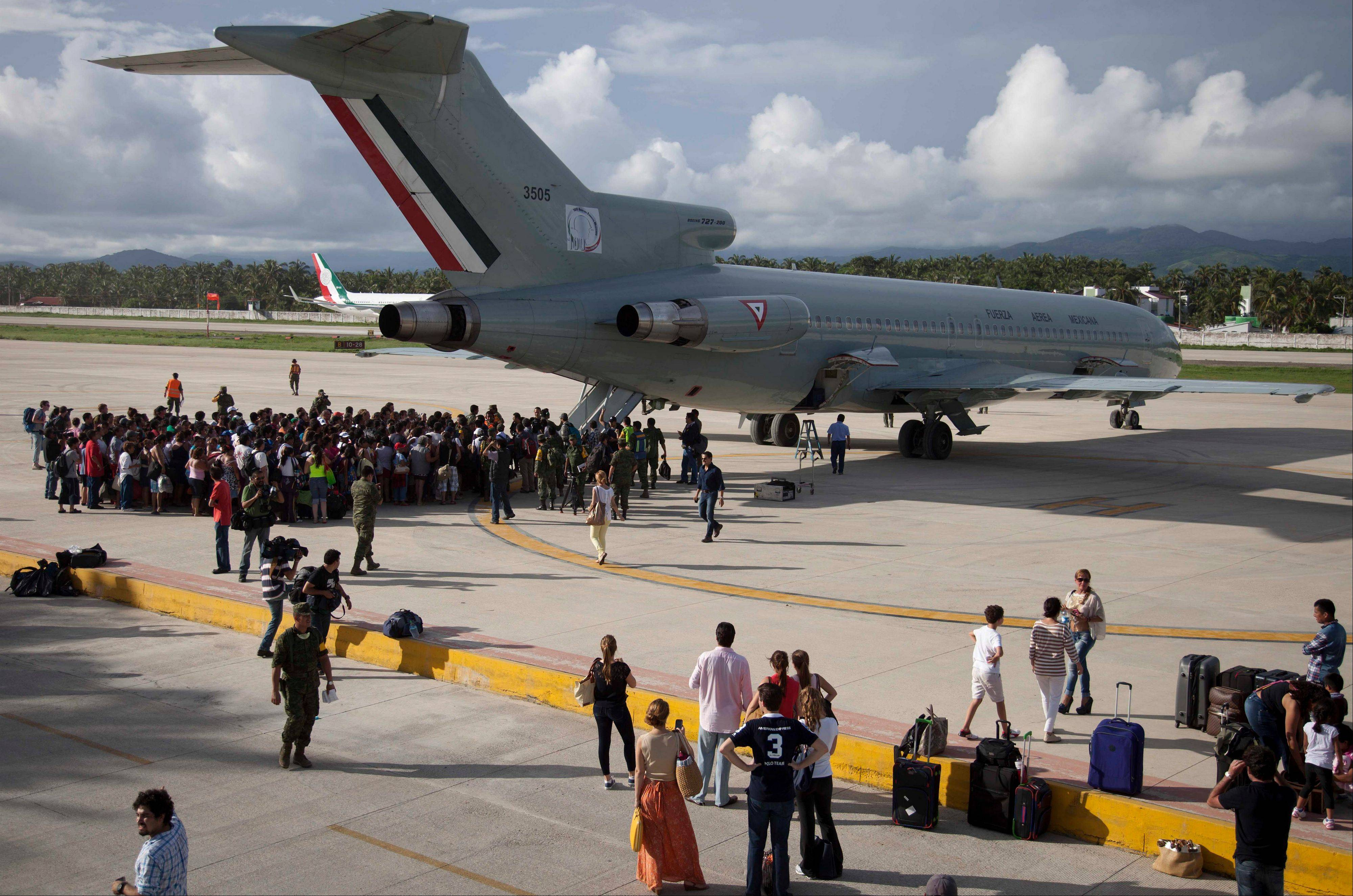 Hundreds of stranded tourists gather around a Mexican Air Force jet as they wait to be evacuated, at the air base in Pie de la Cuesta, near Acapulco, Mexico, Tuesday, Sept. 17, 2013. With roads blocked by landslides, rockslides, floods and collapsed bridges, Acapulco was cut off from road transport after Tropical Storm Manuel made landfall on Sunday. The airport as well, was flooded. Emergency flights began arriving in Acapulco to evacuate at least 40,000 mainly Mexican tourists stranded in the resort city.
