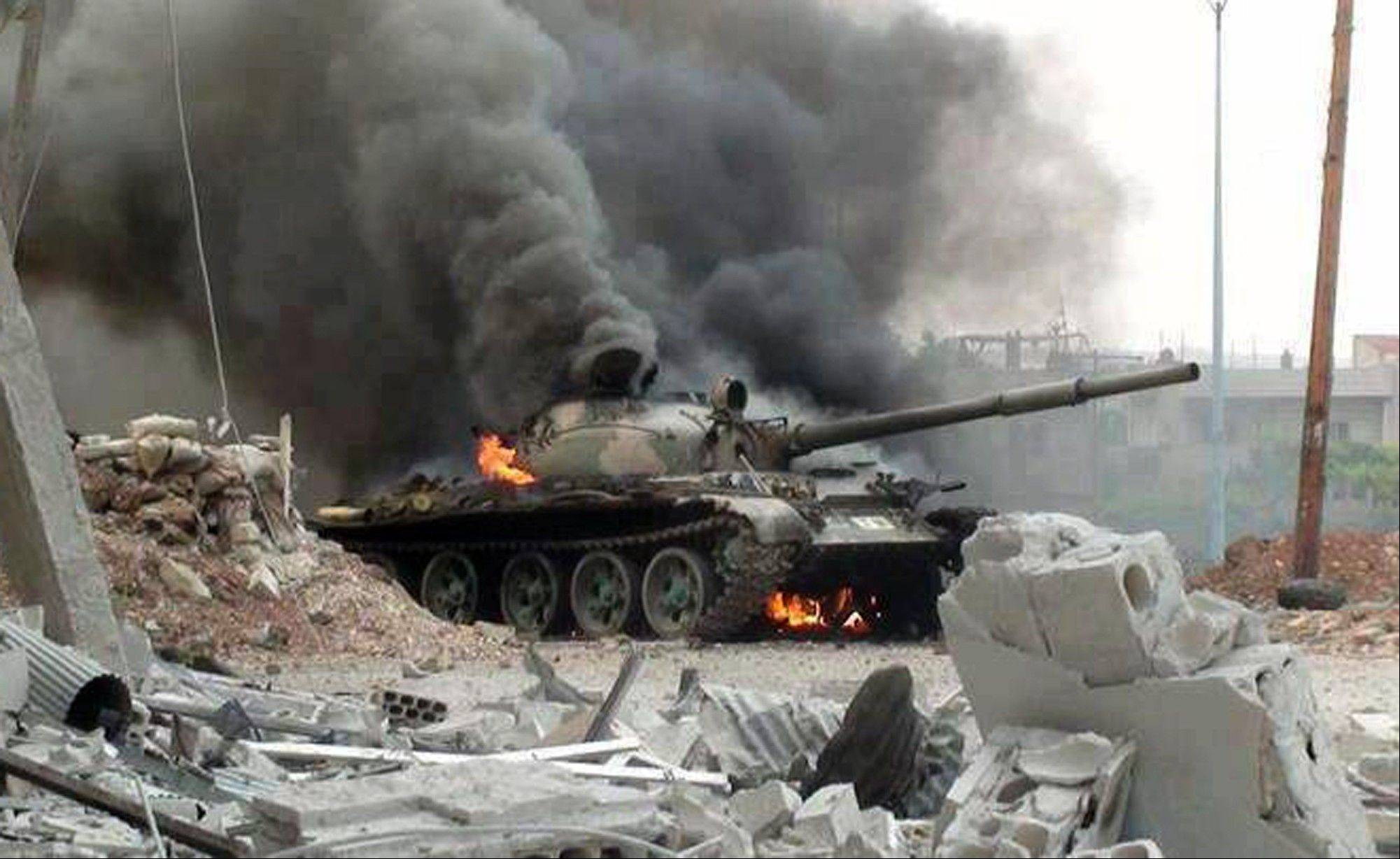This citizen journalism image provided by The Syrian Revolution against Bashar Assad which has been authenticated based on its contents and other AP reporting, shows a Syrian military tank on fire during clashes with Free Syrian army fighters in Joubar, a suburb of Damascus, Syria, Wednesday.