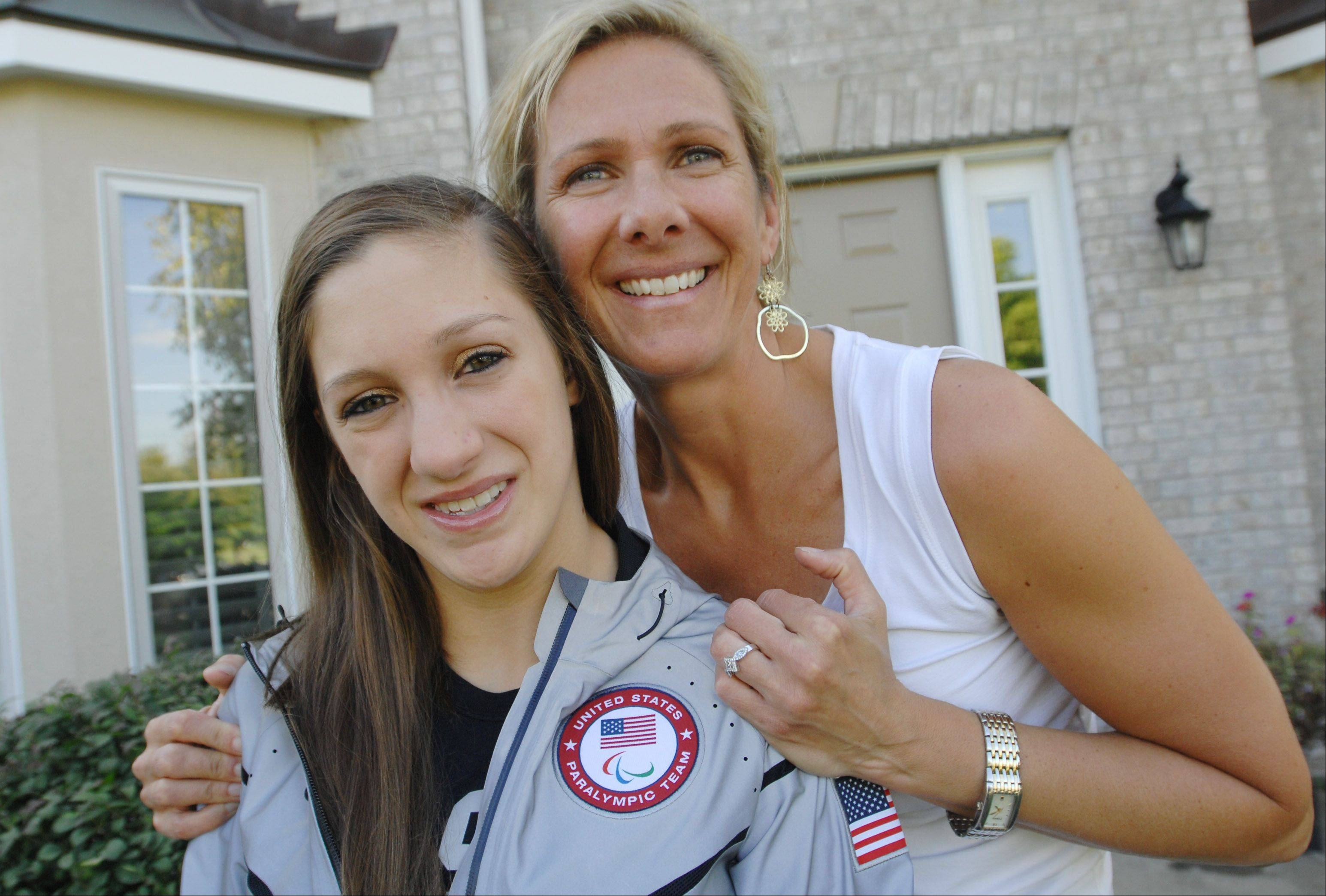 Paralympian swimmer Alyssa Gialamas sports her podium jacket from the 2012 London Games with her mother, Lisa, at their Naperville home. Gialamas, 18, recently won a bronze medal at the International Paralympic Committee Swimming World Championships in Montreal, and is training for the 2016 Paralympics in Rio de Janeiro.