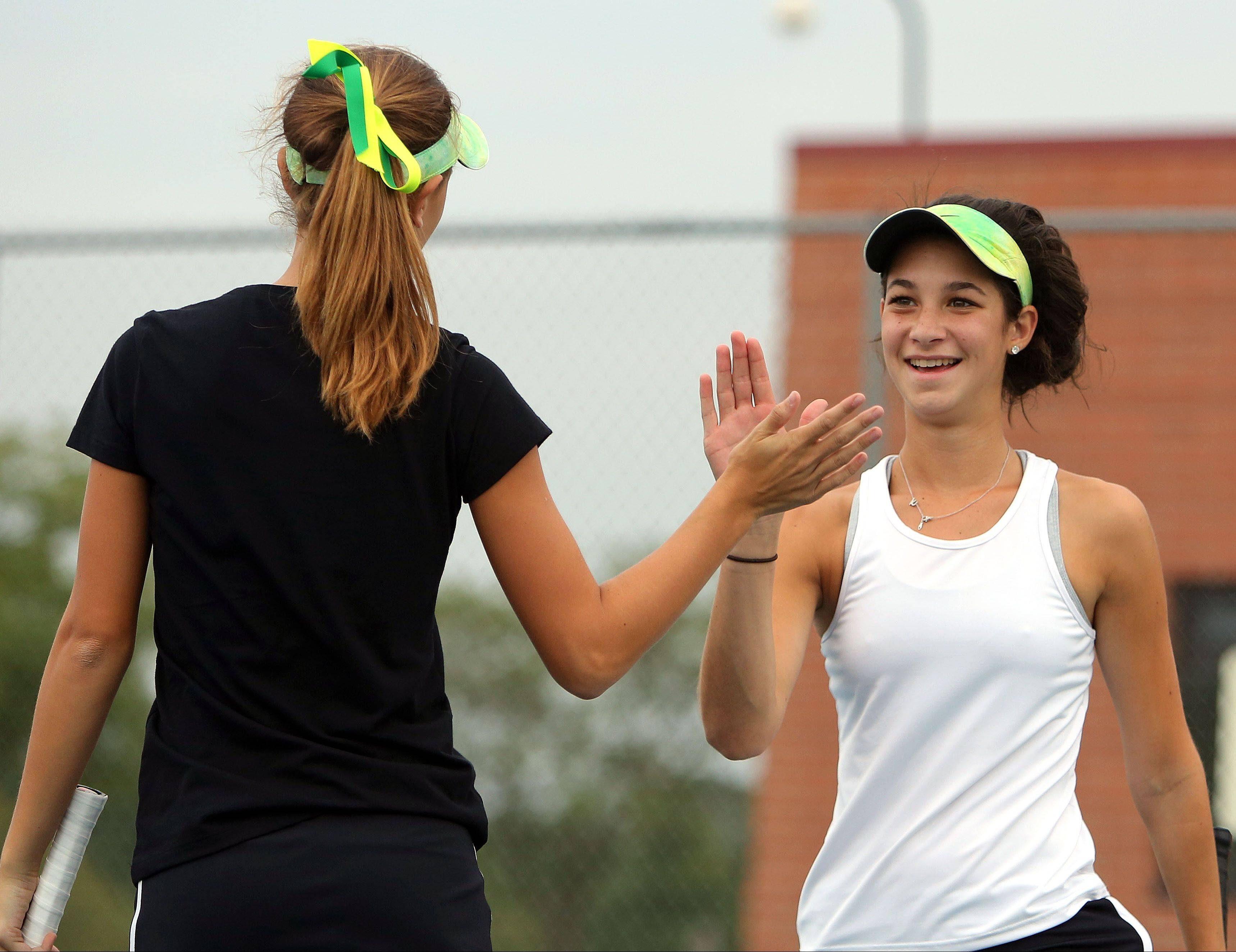 Stevenson's doubles team of Lexxi Kiven, left, and Kendall Kirsch high-five after a point Wednesday at Warren.