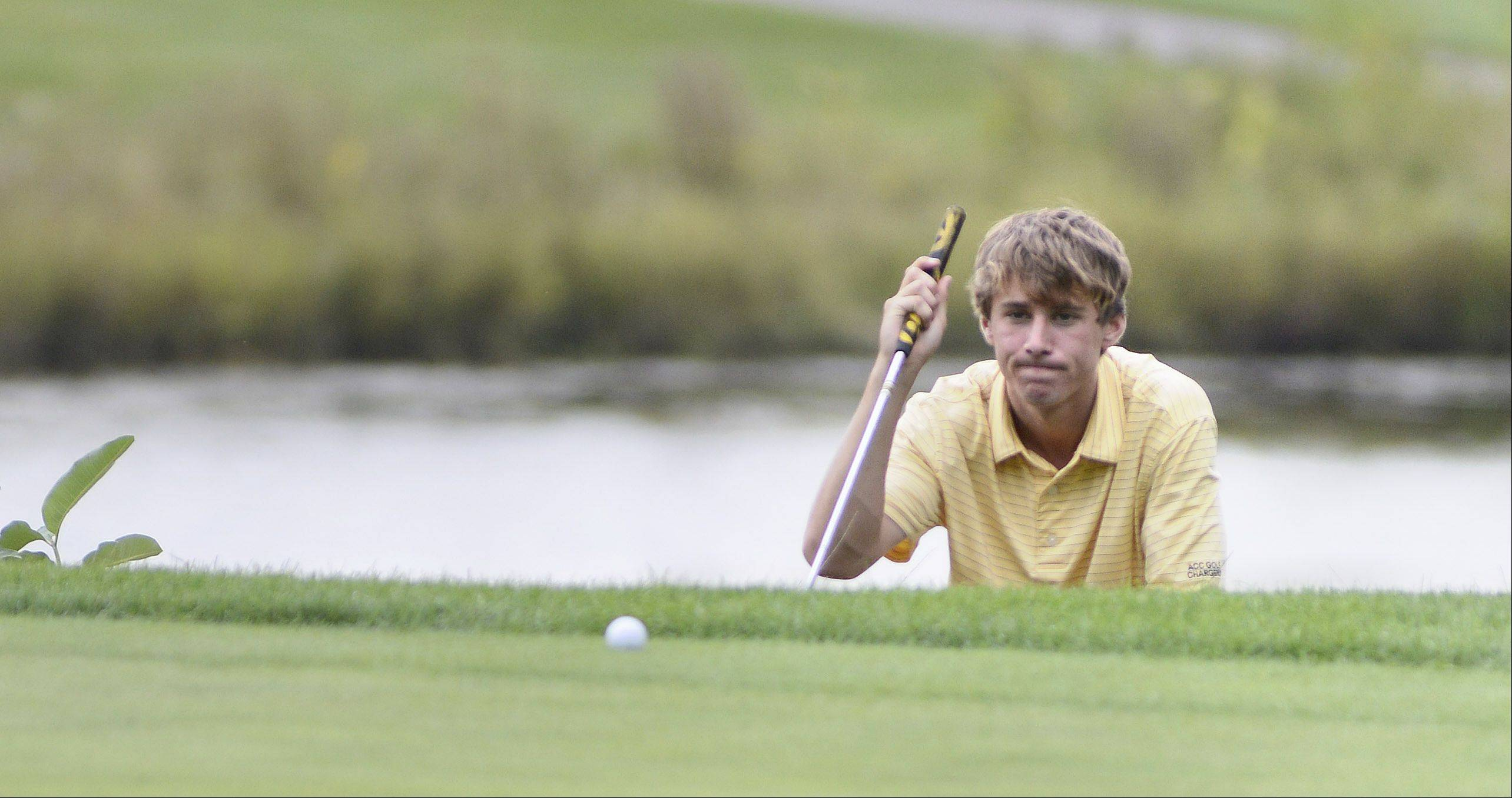 Aurora Central Catholic's Justin Prince judges his shot after hitting the ball out of the sand trap on the sixth hole at Phillips Park Golf Course in Aurora on Wednesday, September 18.