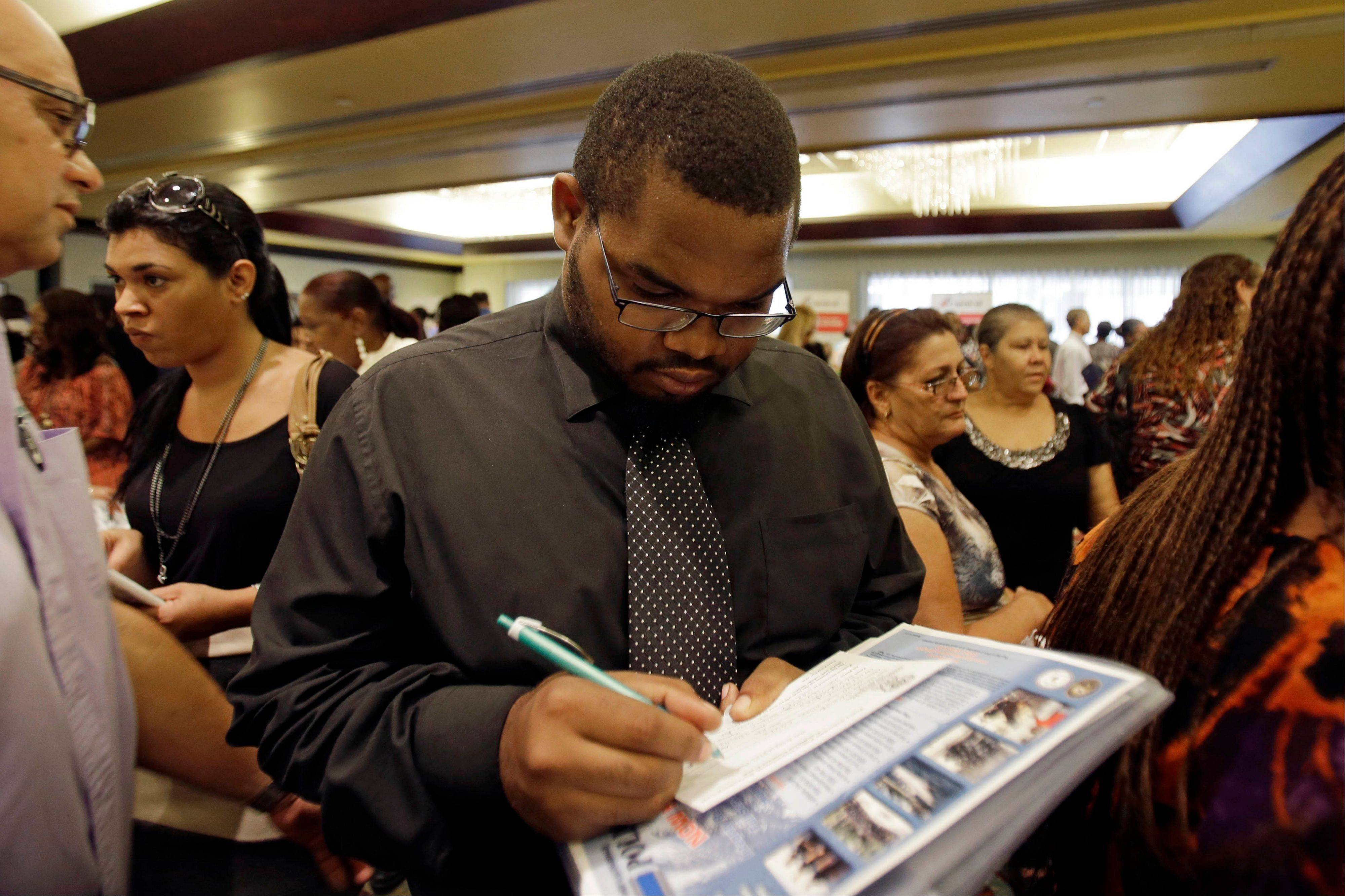 Associated Press Job seeker Kelsey Devoe, of Miramar, Fla., fills out a contact form at a job fair in Miami Lakes, Fla. The number of people seeking U.S. unemployment benefits rose 15,000 last week to a seasonally adjusted 309,000.