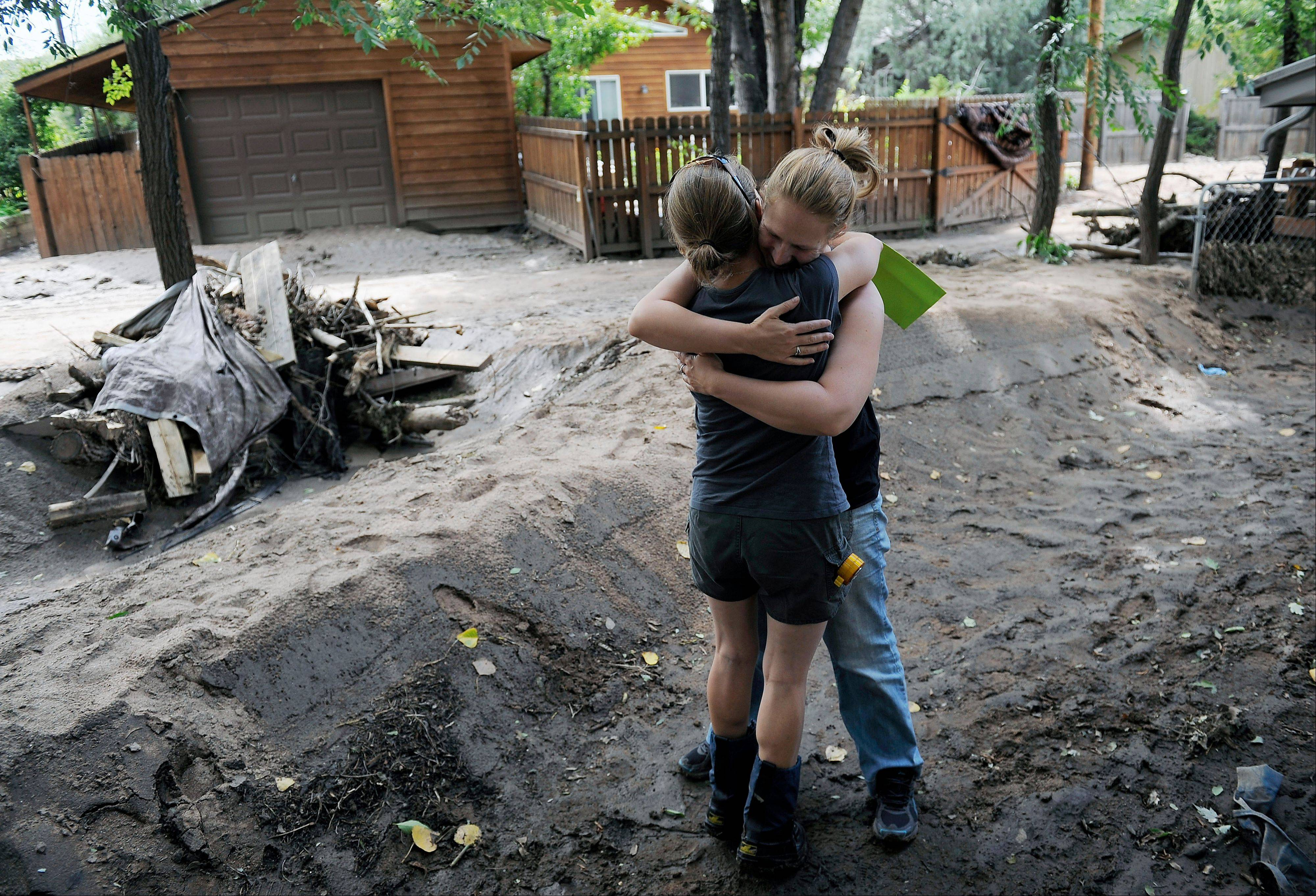 Neighbor Roslynn Regnery, right, gives a hug to Emma Birath, left, as they check on their homes in Lyons, Colo., on Thursday, Sept. 19, 2013. The recovery process has begun all along the front range as people clean out flooded homes and businesses. Local governments are starting to clear debris and repair infrastructure.(AP Photo/Chris Schneider)
