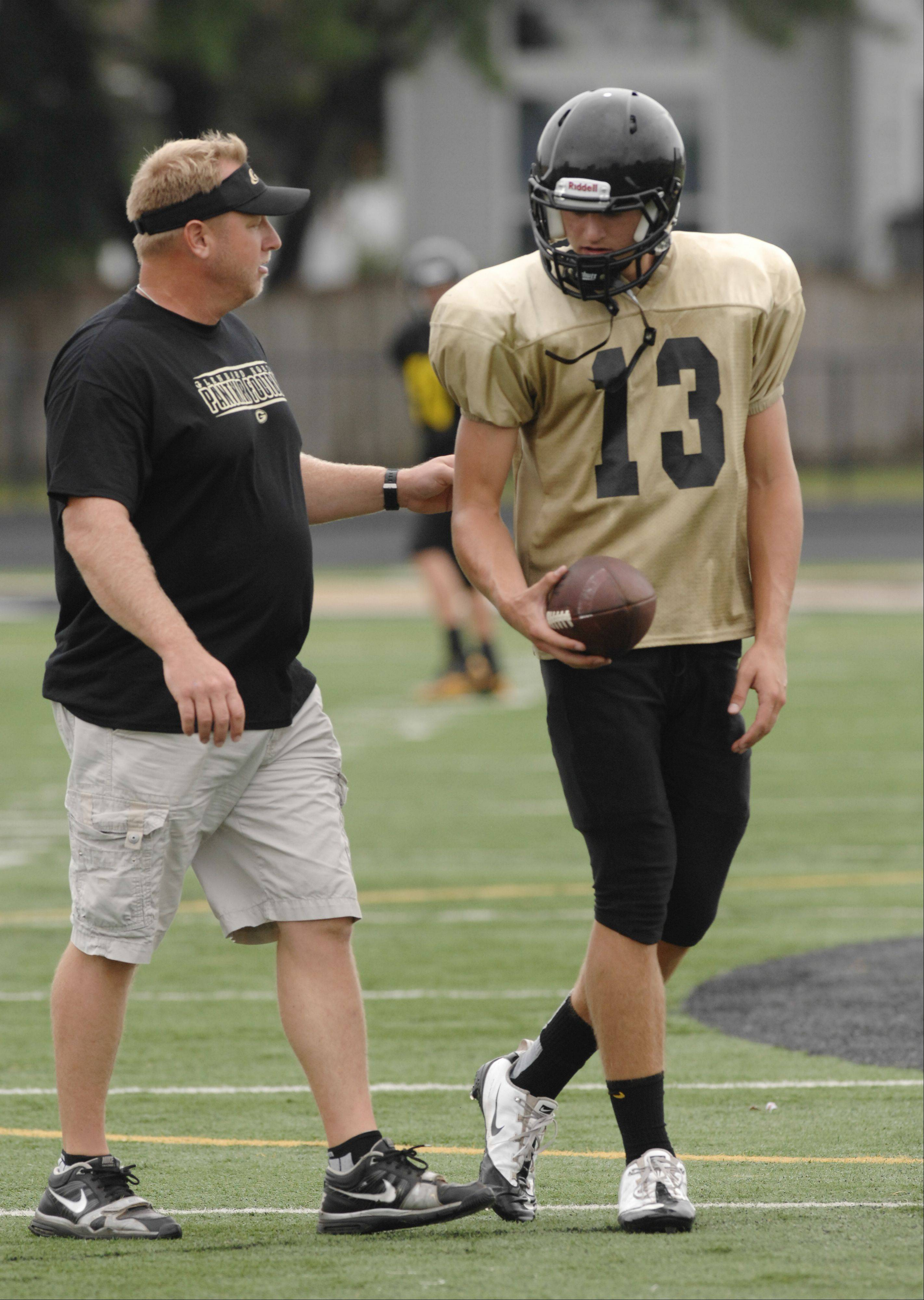 Glenbard North football coach Ryan Wilkens talk with quarterback Brett Gasiorowski during a recent practice. The Panthers might soon drop to Class 7A from Class 8A.