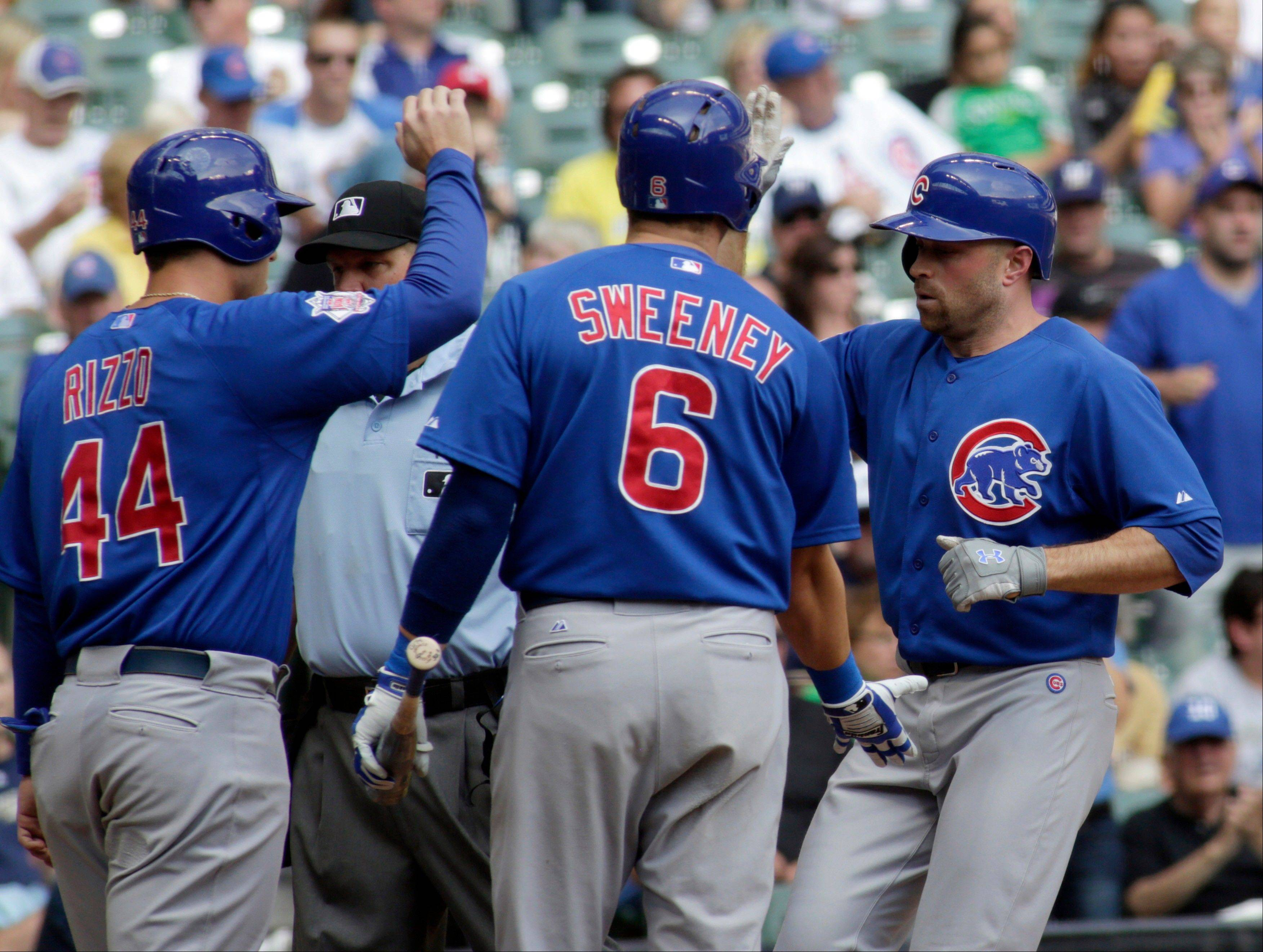 Chicago Cubs' Nate Schierholtz, right, is congratulated by teammates Anthony Rizzo, left, and Ryan Sweeney, center, after hitting a two-run home run against the Milwaukee Brewers during the third inning of a baseball game Thursday, Sept. 19, 2013, in Milwaukee. (AP Photo/Darren Hauck)