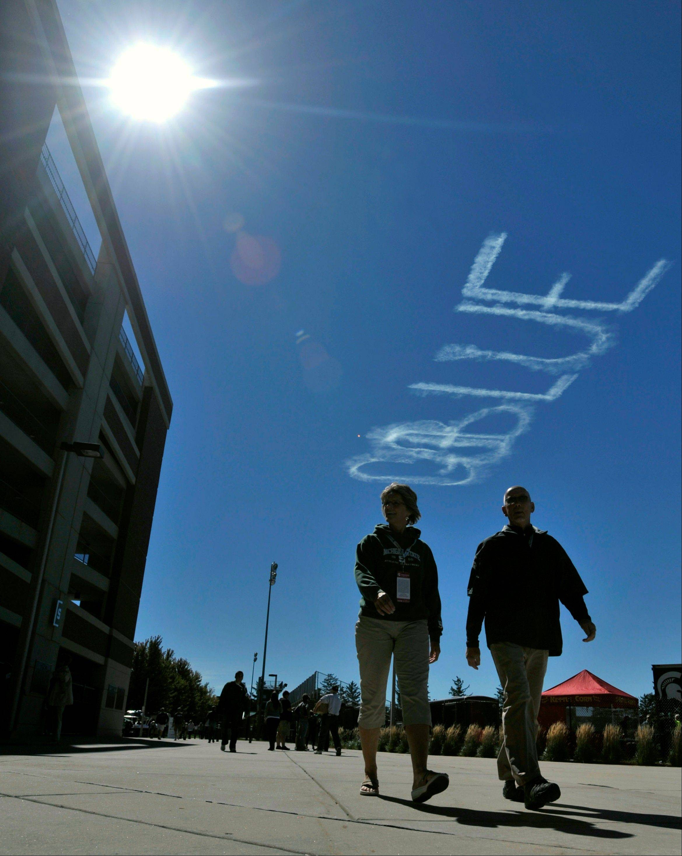 "A skywriter's message reads ""Go Blue,"" a reference to one of the colors of rival Michigan, as fans arrive for a game between Michigan State and Youngstown State last Saturday in East Lansing, Mich."