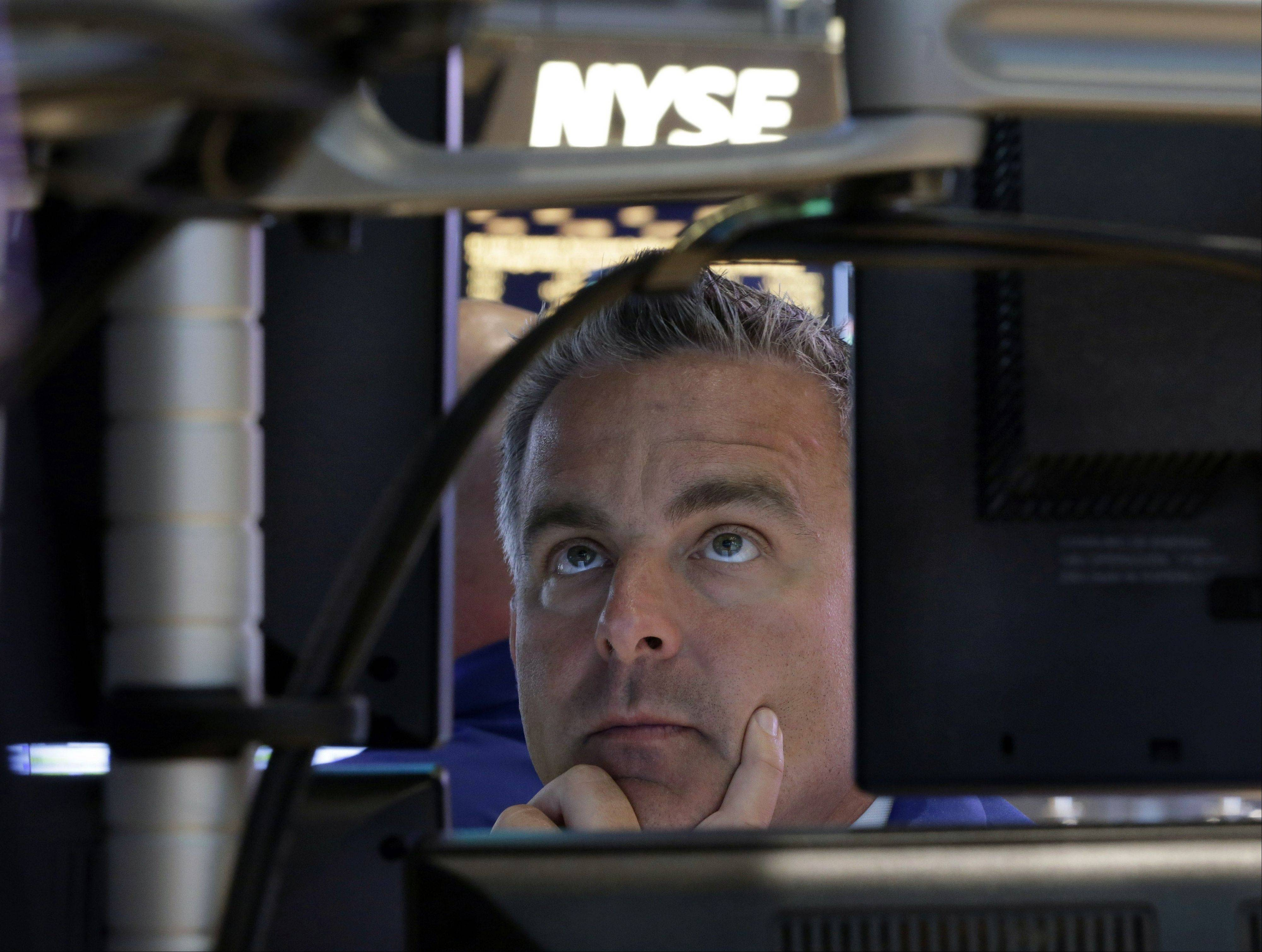 In this Wednesday, Sept. 18, 2013, photo, specialist Christopher Culhane works at his post on the floor of the New York Stock Exchange after the Federal Reserve announcement. Global stock markets surged Thursday after the U.S. Federal Reserve unexpectedly refrained from reducing its massive economic stimulus.