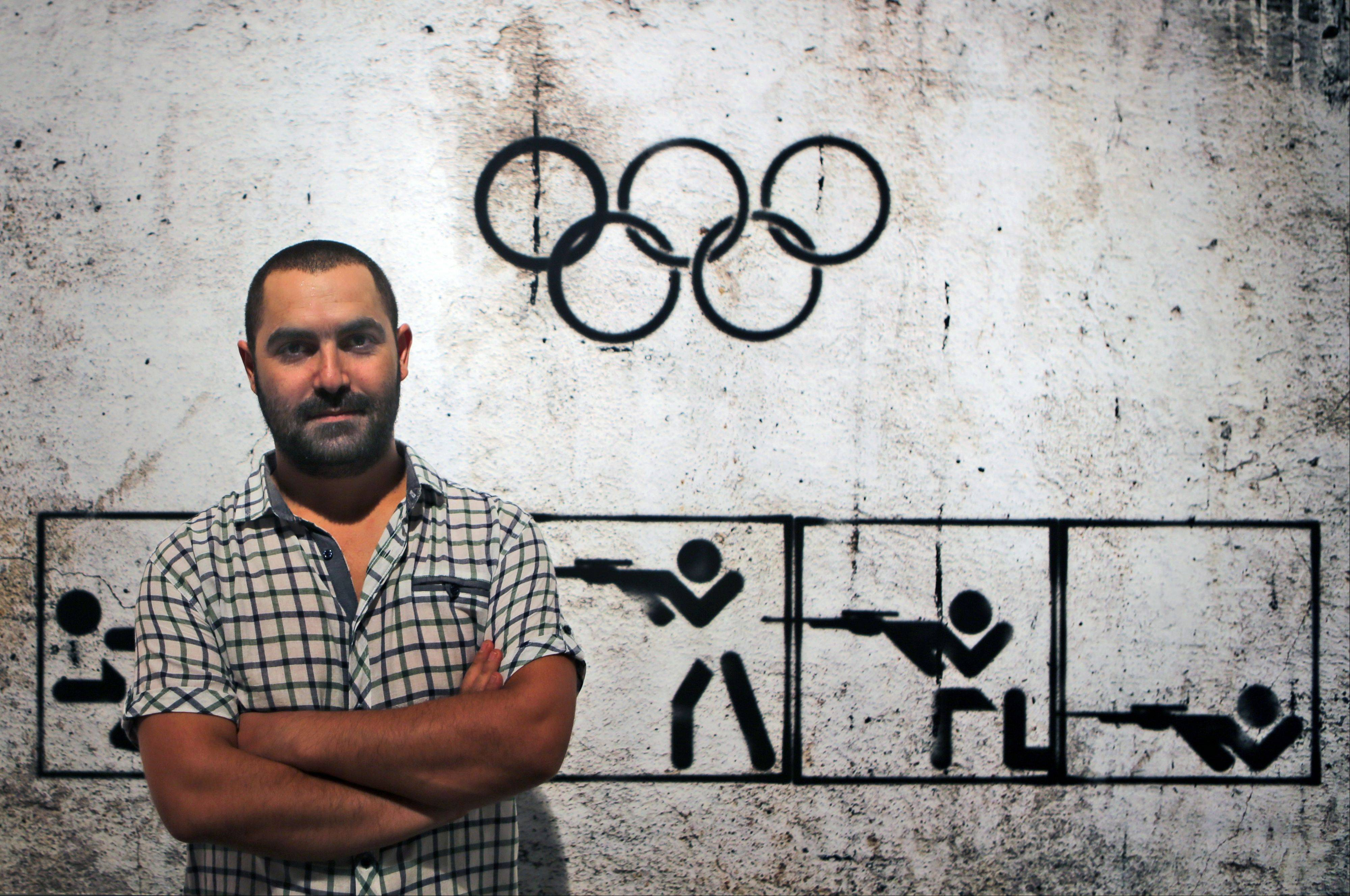 "Syrian artist Tammam Azzam, 23, poses in front of one of his works, a digital print titled ""Syrian Olympic"" during the Young Collectors Auction at Ayyam gallery in Dubai, United Arab Emirates. The auction Monday in Dubai's evolving art district served as a window into a small but forward-looking effort to save one niche of Syria's artistic community with no end in sight to the civil war."