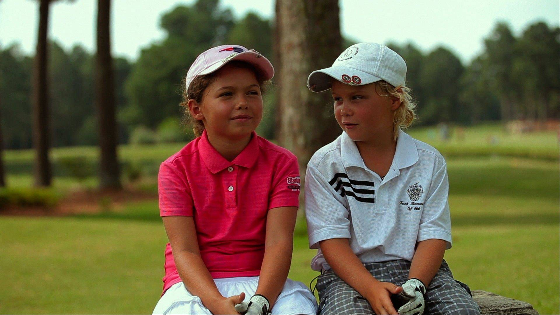 "Kid golfers Alexa Pano and Allan Kournikova rest between takes on the set of the sports documentary ""The Short Game."""