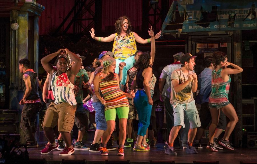 "Beautician Daniela (Keely Vasquez), aloft, whips up the crowd to celebrate a ""Carnaval Del Barrio"" in the Tony Award-winning musical ""In the Heights"" at the Paramount Theatre in Aurora."