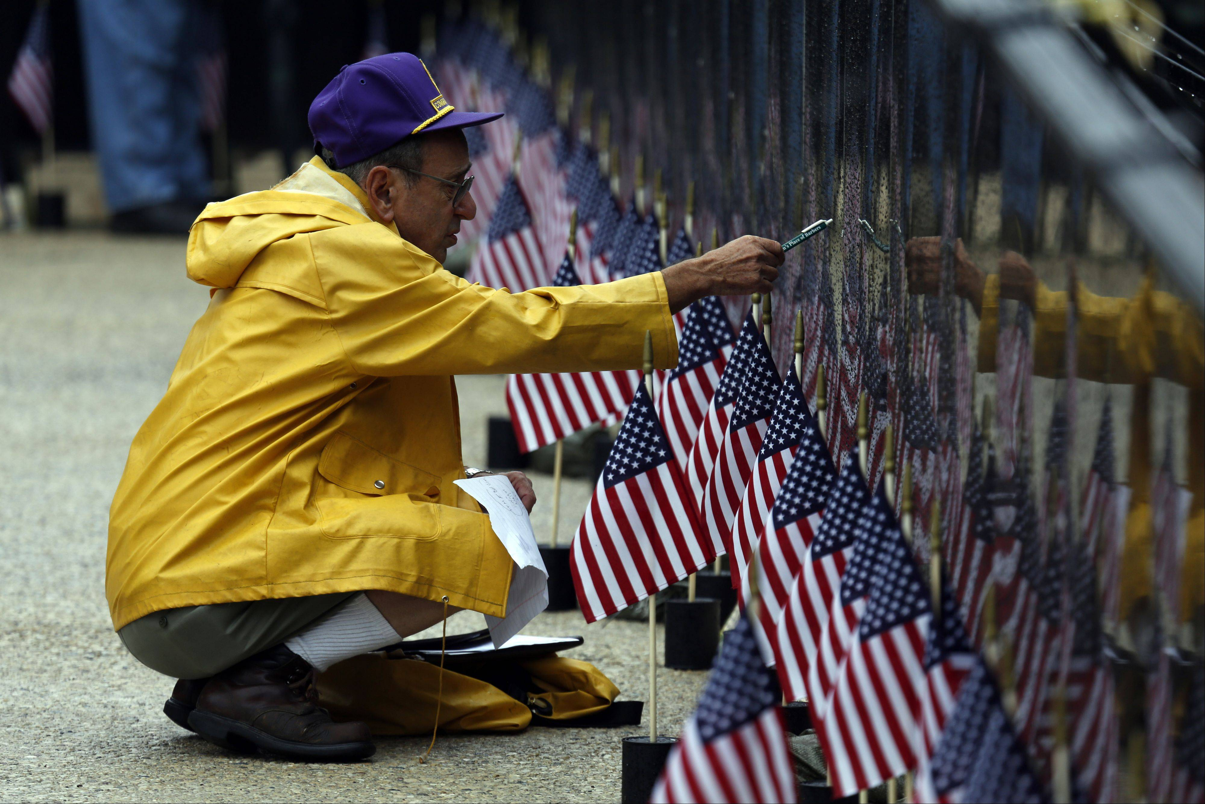 Charles Fox of Elgin, who served in the Army 1st Battalion, 26th Infantry in 1967-68, looks at the wall for the names of his 18 friends killed in one day.