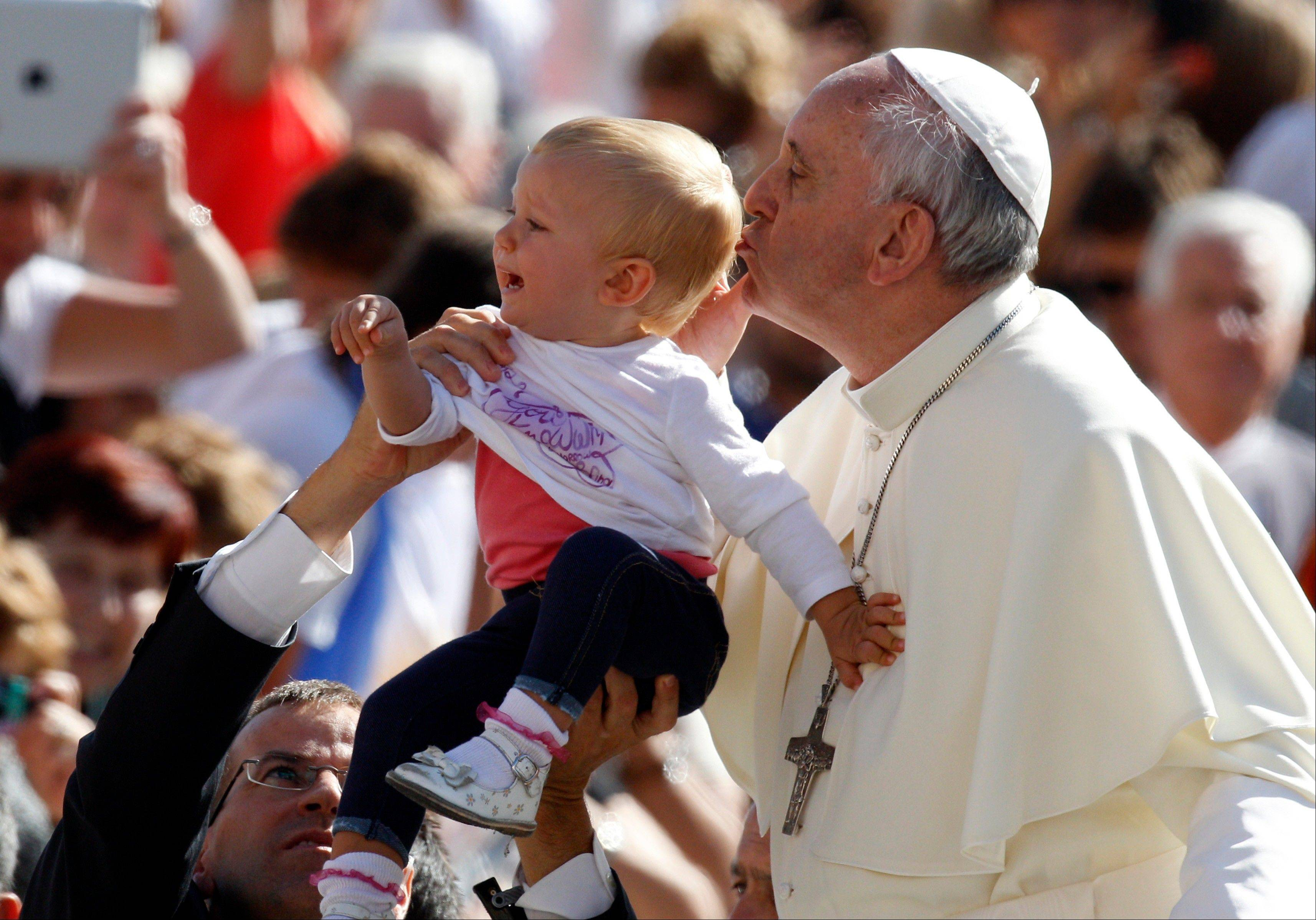 Pope Francis kisses a child as he arrives for his weekly general audience in St. Peter's Square at the Vatican, Wednesday, Sept. 18, 2013.