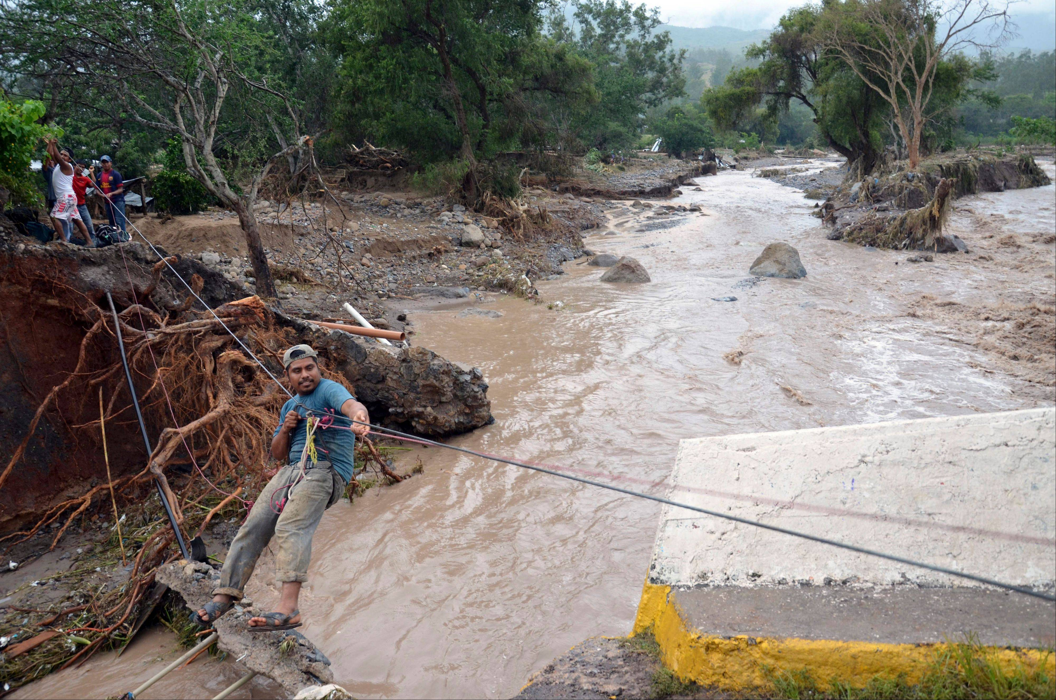 A man uses a makeshift zip line to cross a river after a bridge collapsed under the force of the rains caused by Tropical Storm Manuel near the town of Petaquillas, Mexico, Wednesday, Sept. 18, 2013.