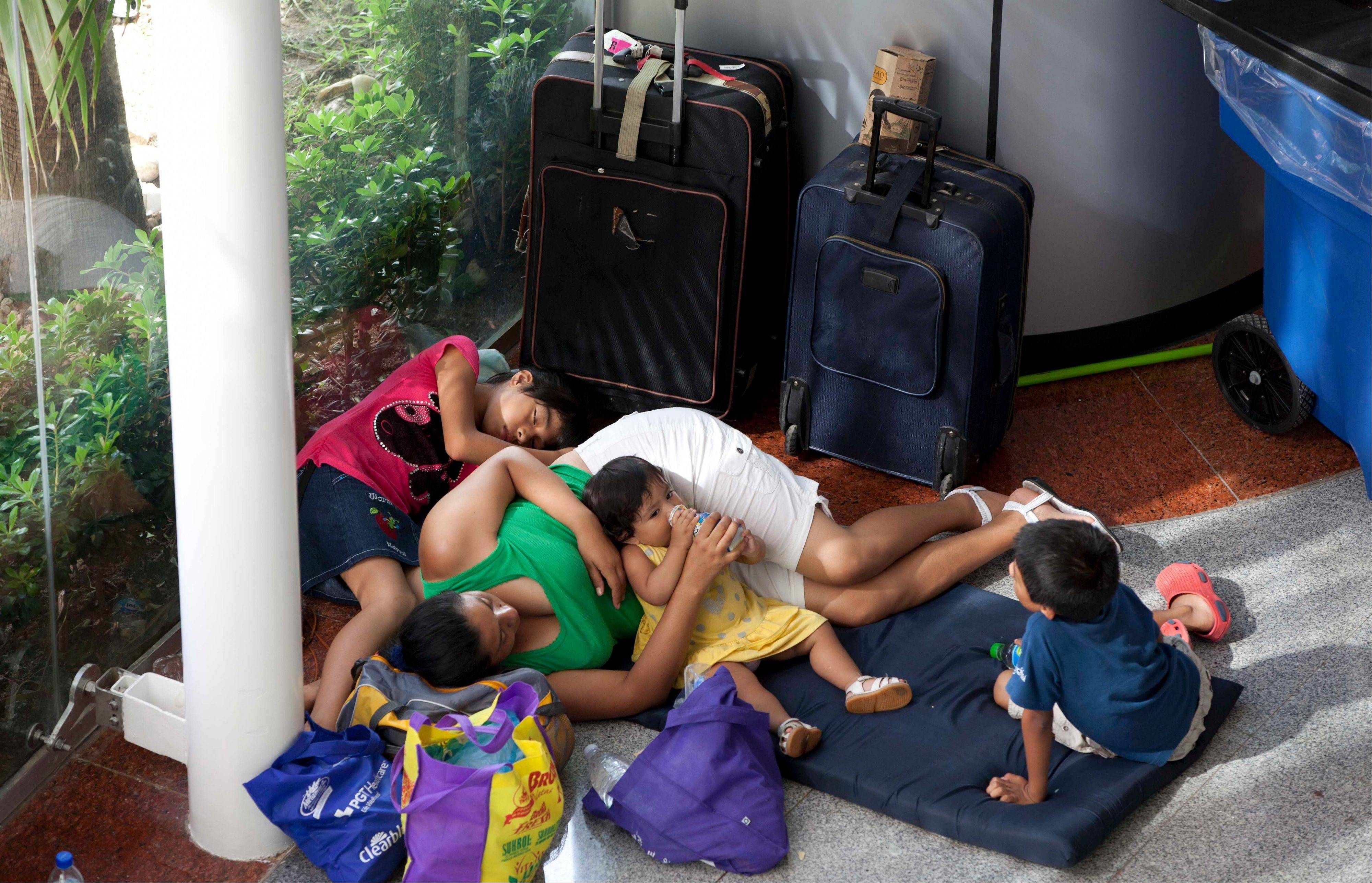 A family rests in a shelter as they wait to be ferried out by air, south of Acapulco, in Punta Diamante, Mexico, Wednesday, Sept. 18, 2013.