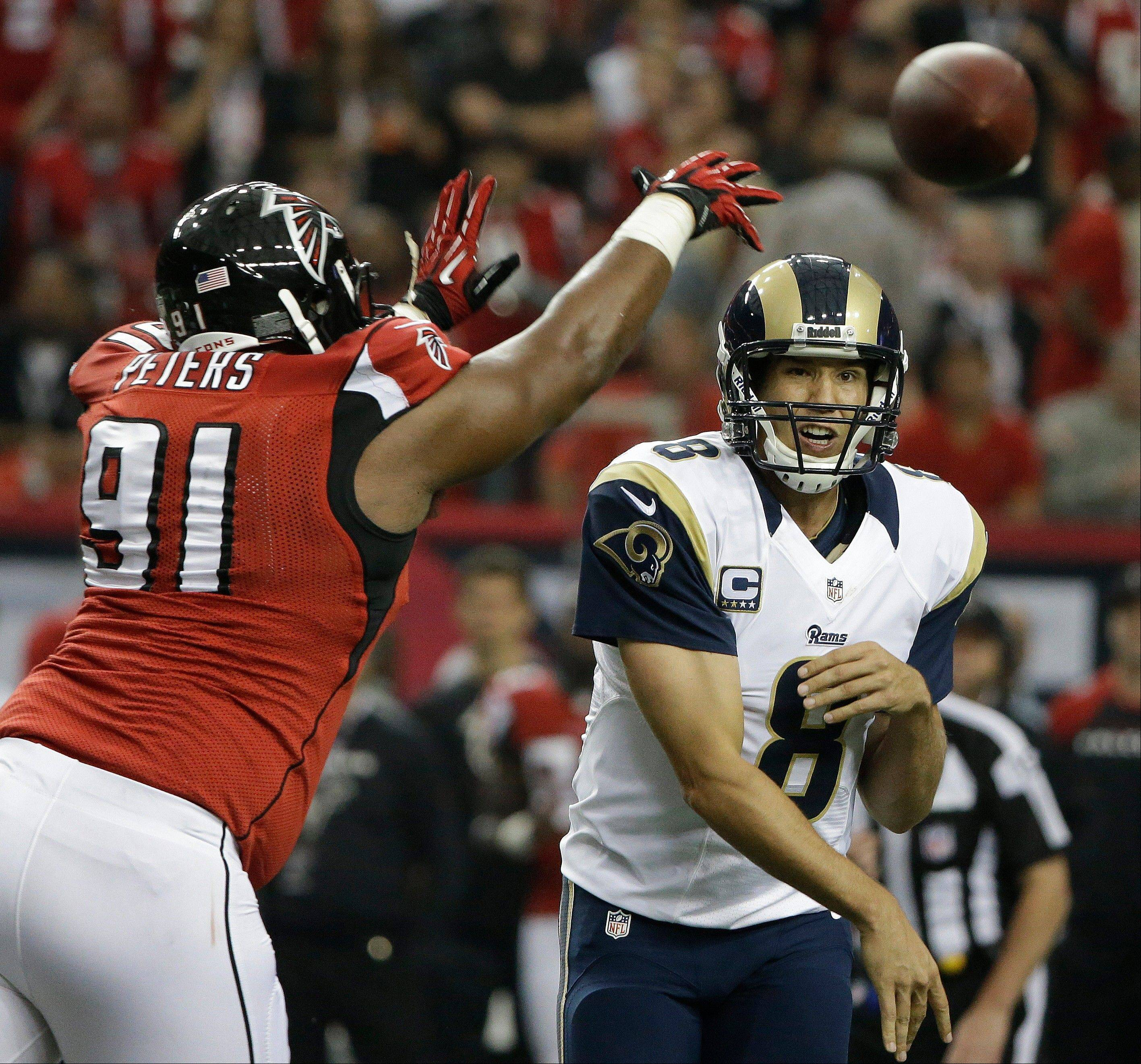 St. Louis Rams quarterback Sam Bradford (8) throws under pressure from Atlanta Falcons defensive tackle Corey Peters (91) during the first half of an NFL football game, Sunday, Sept. 15, 2013, in Atlanta.