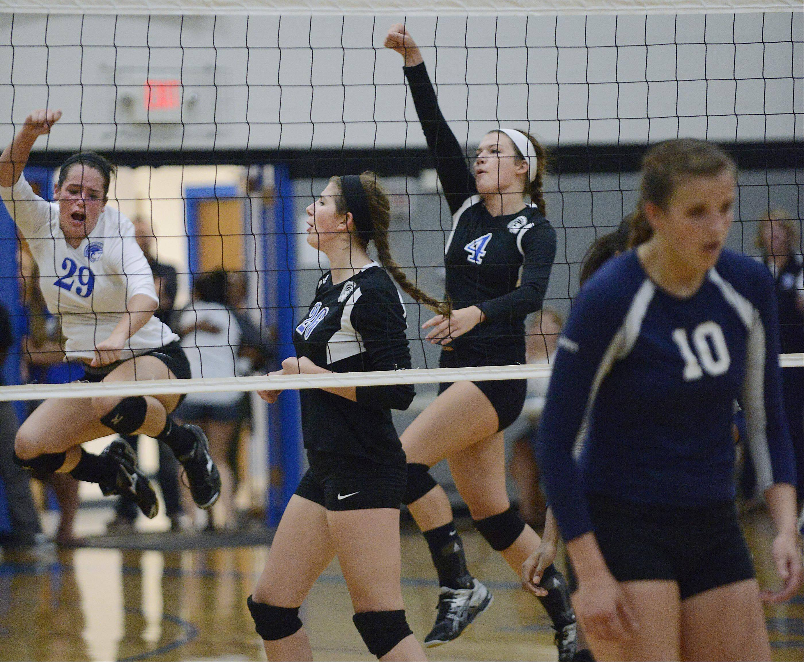 Westminster Christian's Cassidy Finnegan, left, Savannah Dutcher, and Courtney Gnan, right, celebrate a point as Harvest Christian's Sydney Doby turns away Thursday in Elgin.
