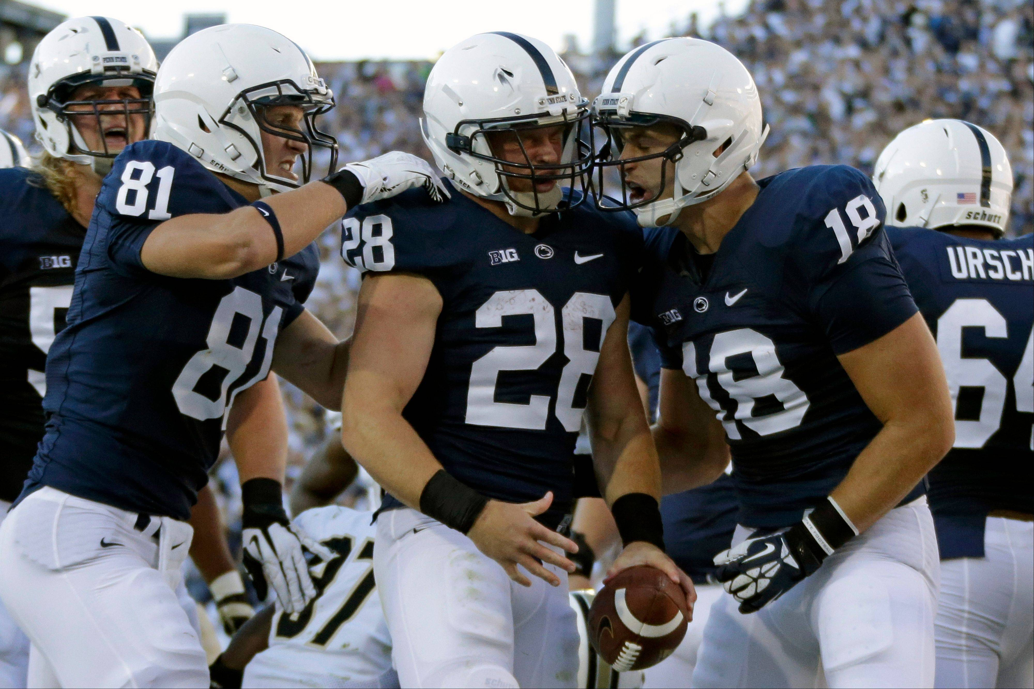 Penn State running back Zach Zwinak (28) celebrates with teammates Adam Breneman (81) and Jesse James (18) after rushing for a touchdown during the first quarter of last weekend's game against Central Florida in State College, Pa.