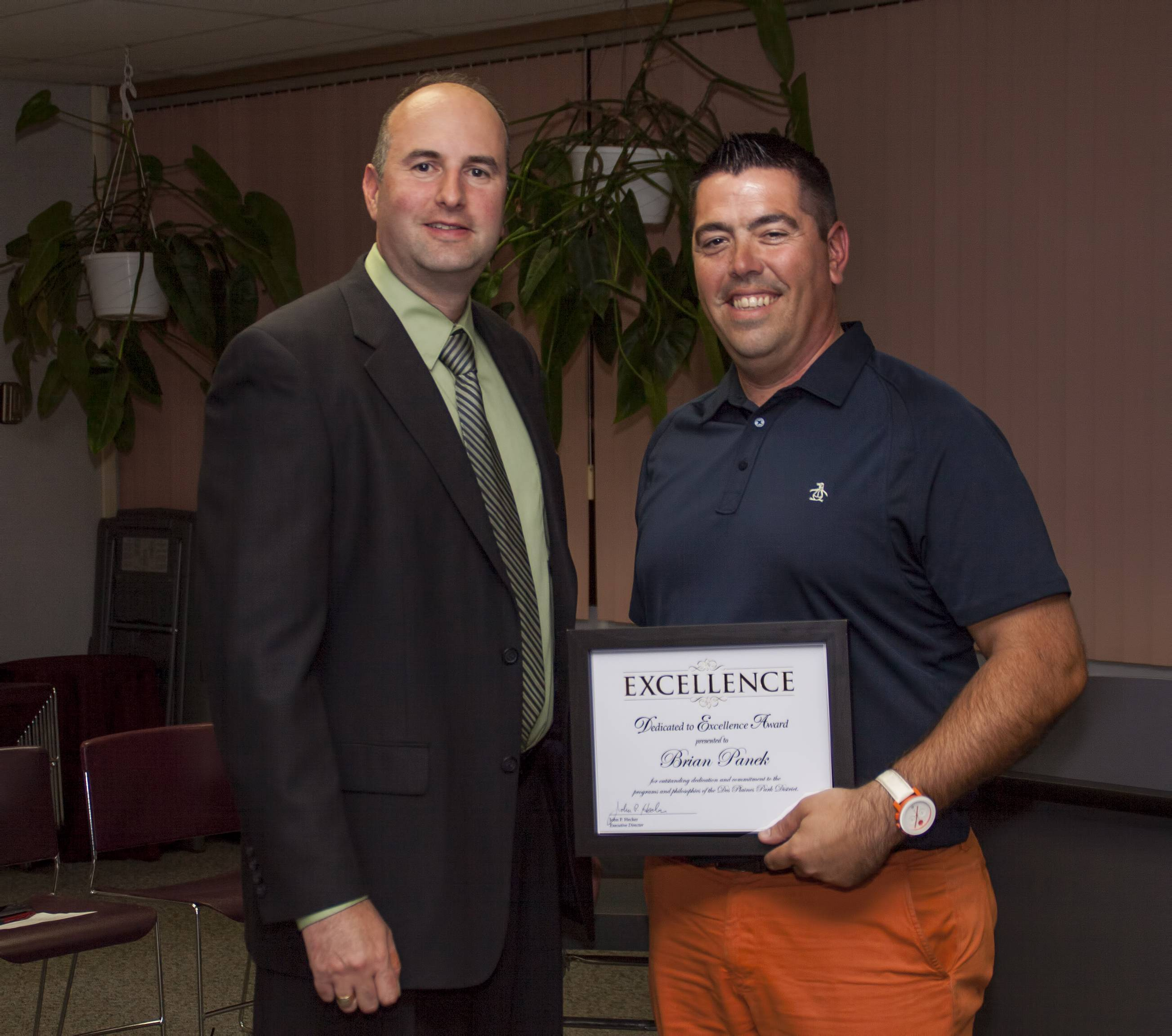Brian Panek (right) receives his Dedicated to Excellence Award from Don Miletic at the Park Board Meeting on September 17.