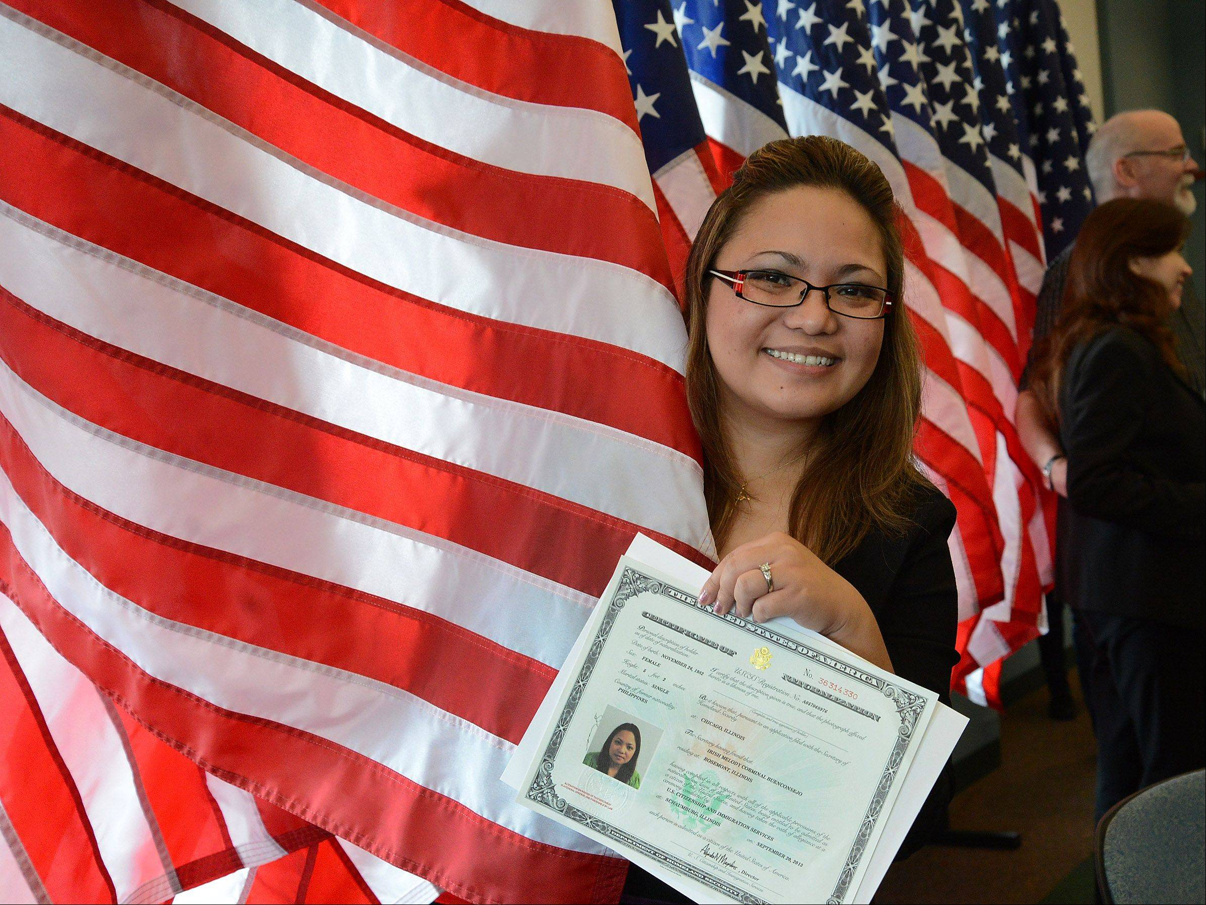 Irish Melody Buenconsejo of Rosemont wraps herself in the American flag after receiving her certificate of citizenship during a naturalization ceremony Friday in Schaumburg.