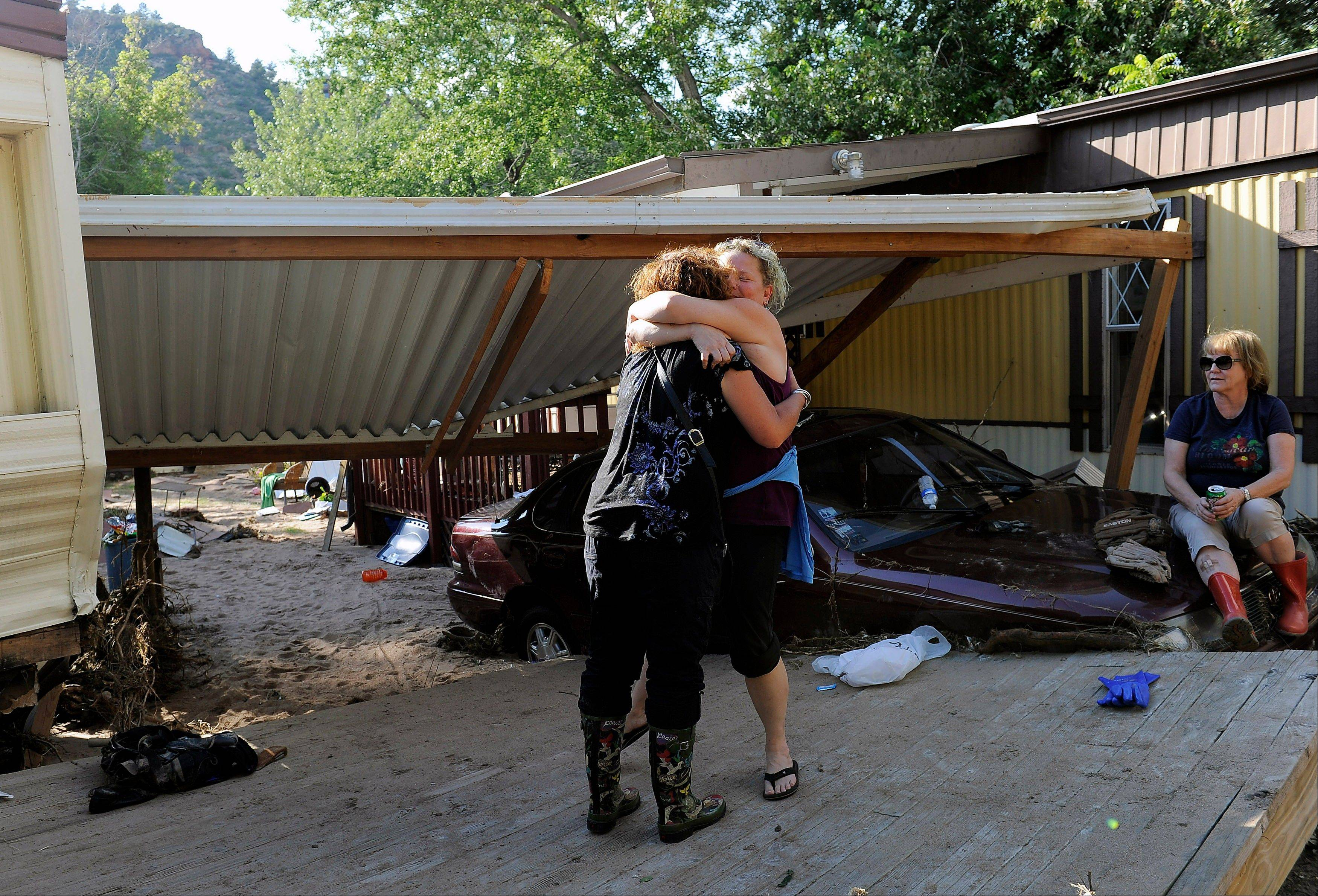 Molly Morton, left, hugs Jenna Brink, center right, outside Brink�s flood-damaged trailer at the River Bend Mobile Home Park in Lyons, Colo., as Brink�s mother, Christine Brink takes a break from clearing belongings from the trailer on Thursday, Sept. 19, 2013. Hundreds of evacuees were allowed past National Guard roadblocks Thursday to find a scene of tangled power lines, downed utility poles, and mud-caked homes and vehicles.