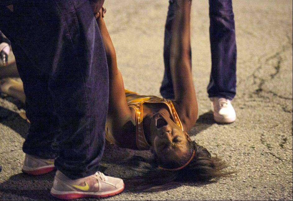 A woman becomes emotional Thursday near the scene of a shooting at Cornell Square Park in Chicago�s Back of the Yard neighborhood that left multiple victims, including a 3-year-old boy. Thursday night�s attack was the latest violence in a city that has struggled to stop such shootings by increasing police patrols.