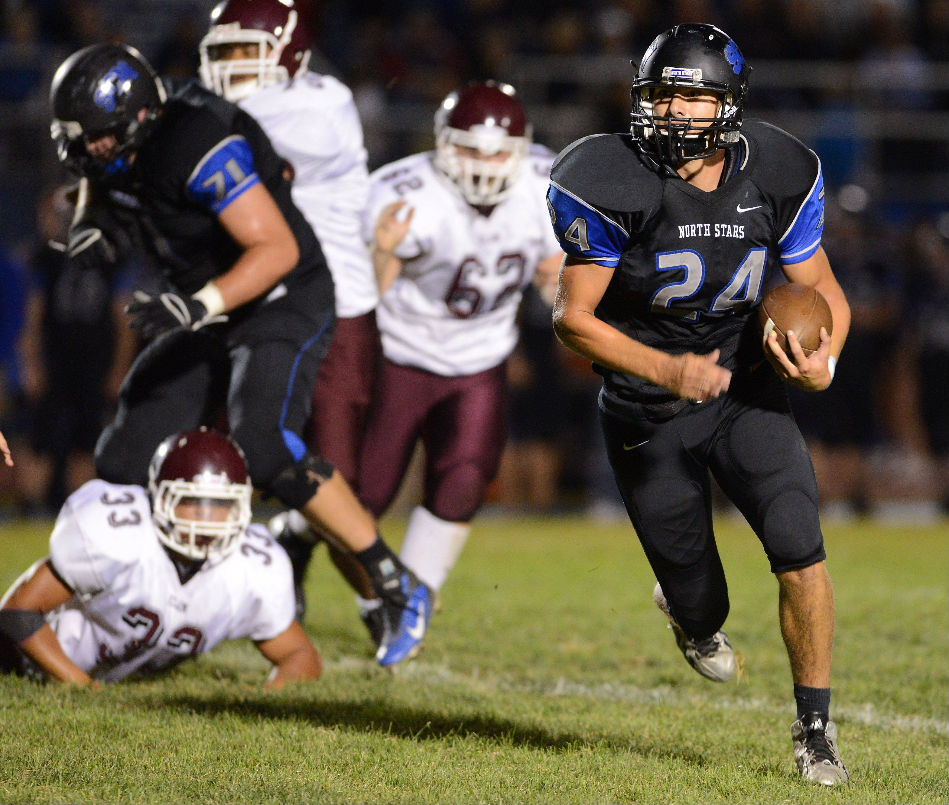 St. Charles North�s Evan Kurtz (24) leaves several broken tackles in his wake en route to a big gain against Elgin during Friday�s game in St. Charles.