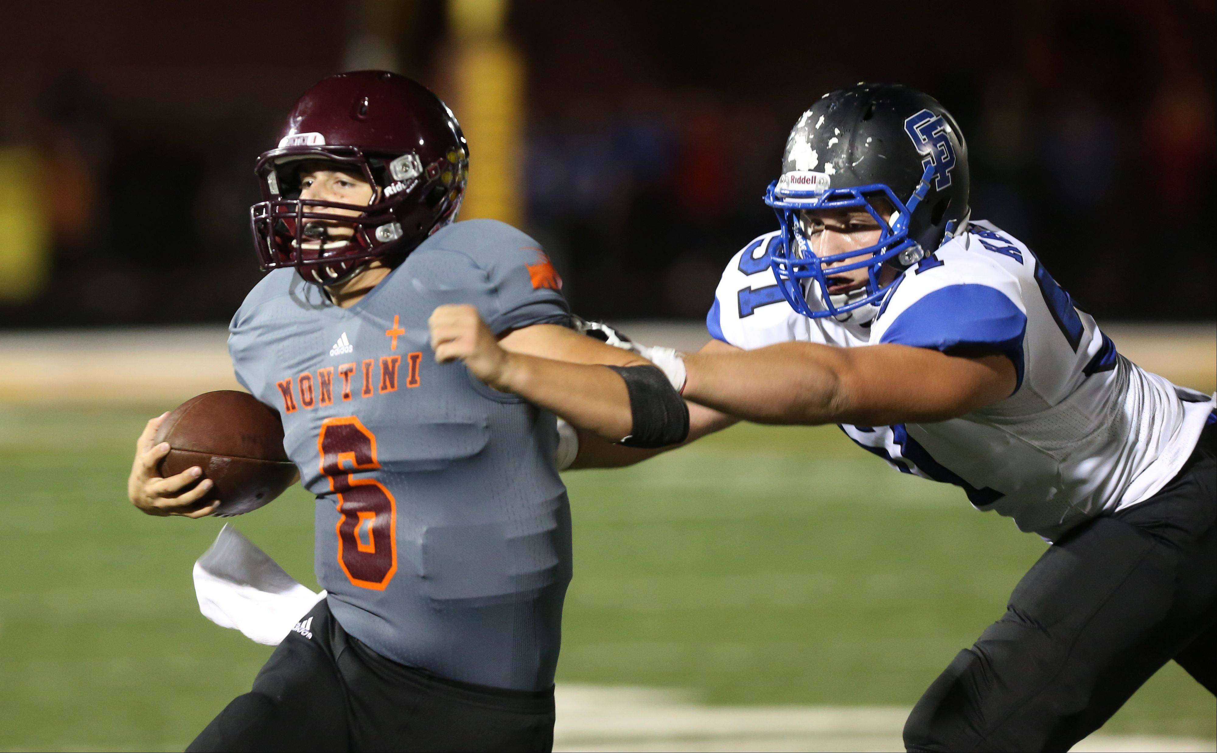 Montini quarterback Alexander Wills, left, is pursued by St. Francis' James Kalfas Friday night.