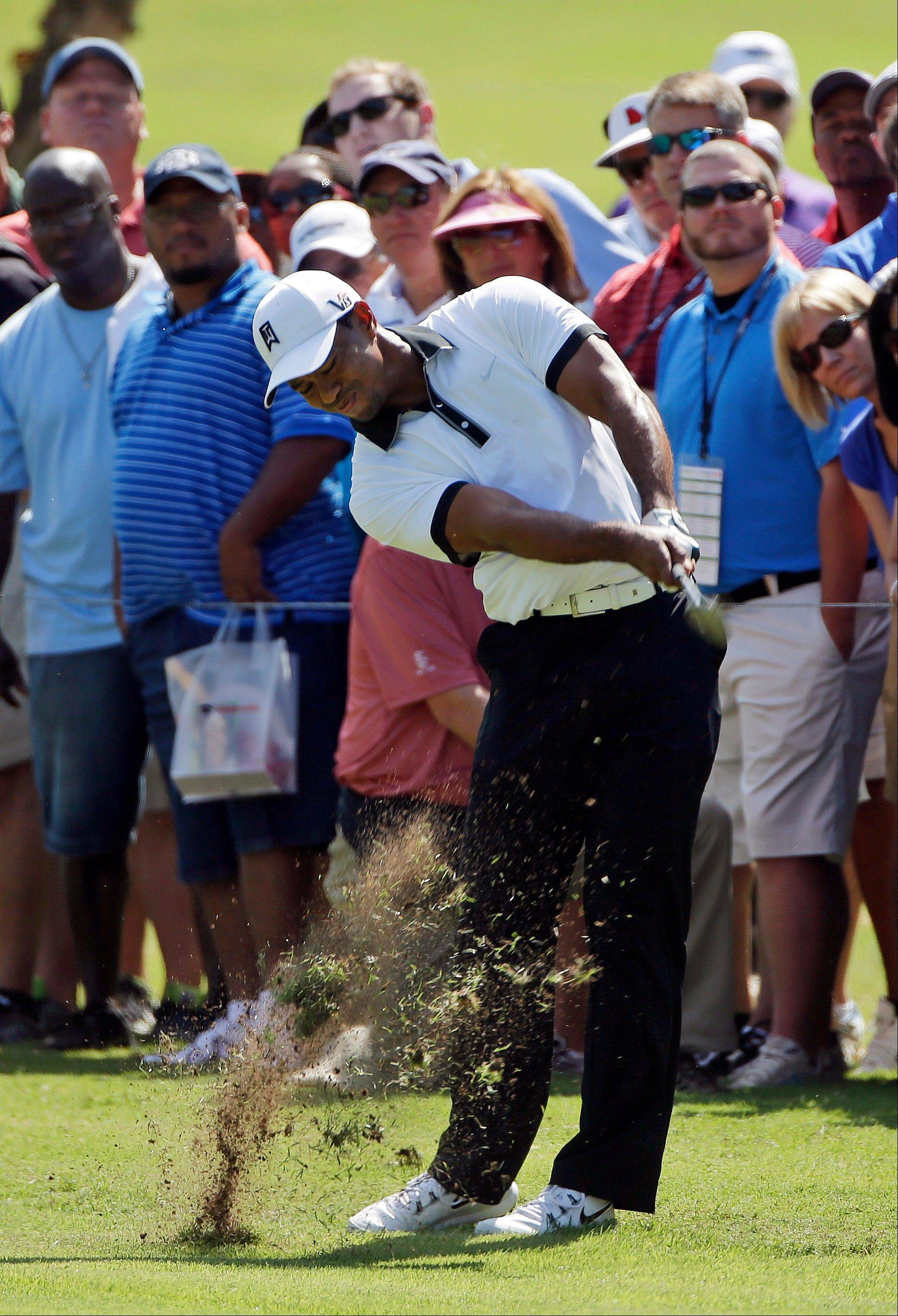 Tiger Woods hits from the rough Friday at the Tour Championship tournament at East Lake Golf Club in Atlanta. He finished the round with a 71.