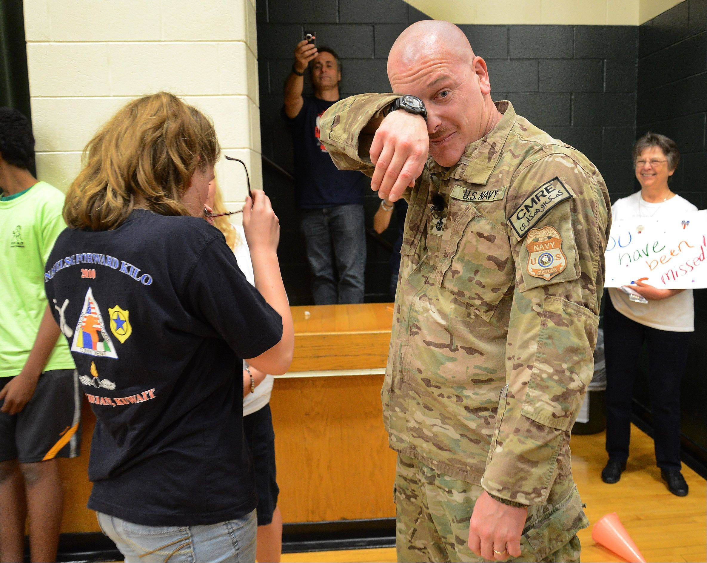 Navy Chief Gunner's Mate Patrick Fissette wipes away tears as he surprises his daughter, Kailey, at Mead Junior High School in Elk Grove Village Friday after returning home from his last tour of duty.