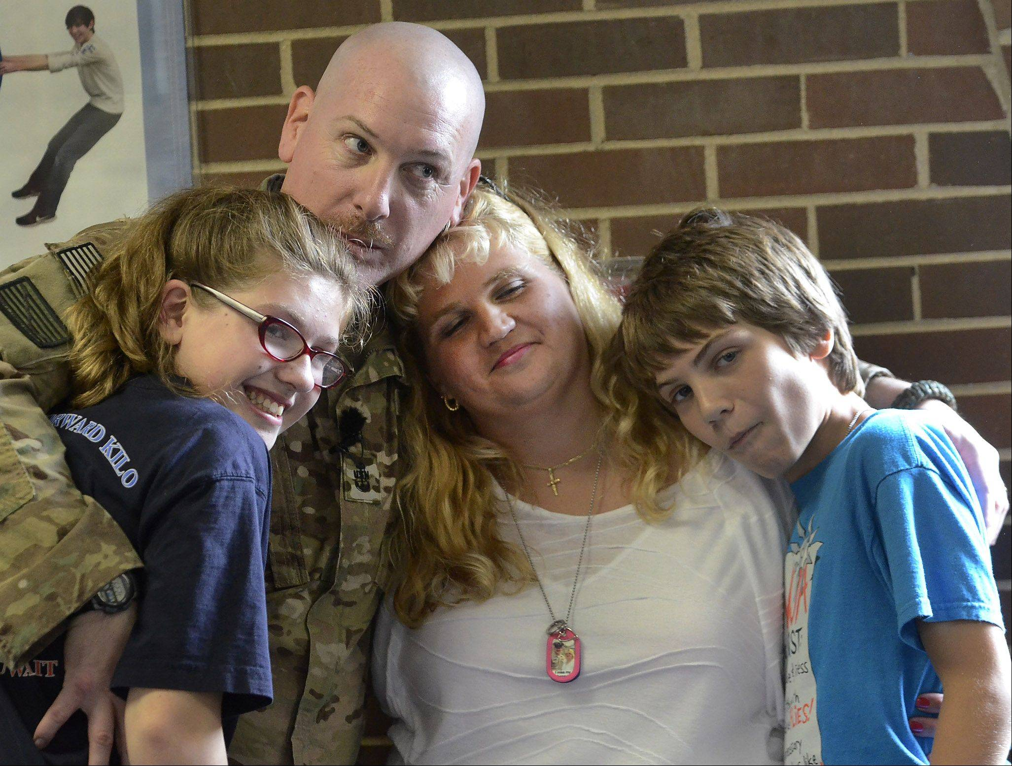 Navy Chief Gunner's Mate Patrick Fissette reunites with his family, daughter Kailey, wife Kim and son Tristan after surprising his children at Mead Junior High School in Elk Grove Village Friday after returning home from his last tour of duty.