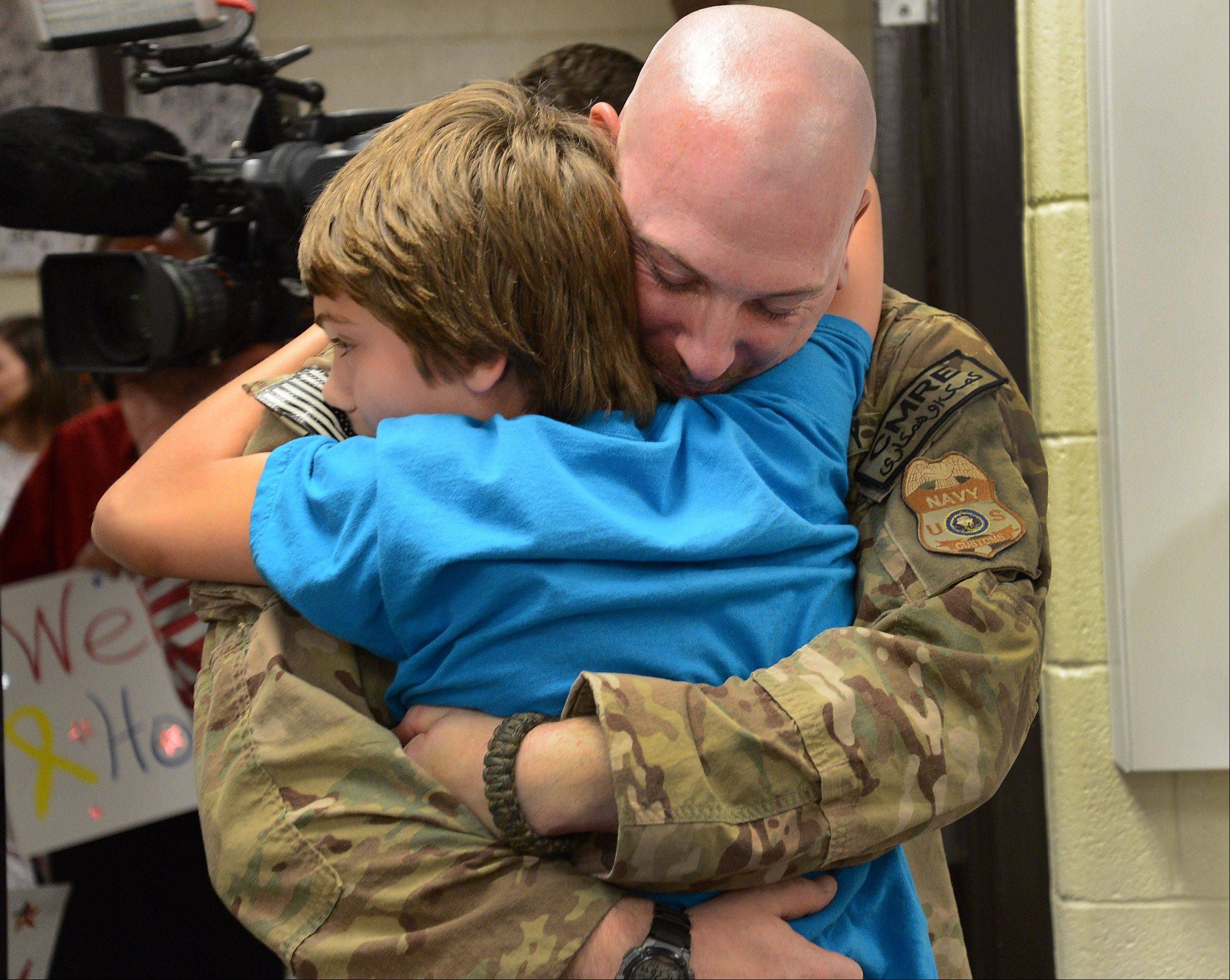 Navy Chief Gunner's Mate Patrick Fissette embraces son Tristan on Friday at Mead Junior High School.