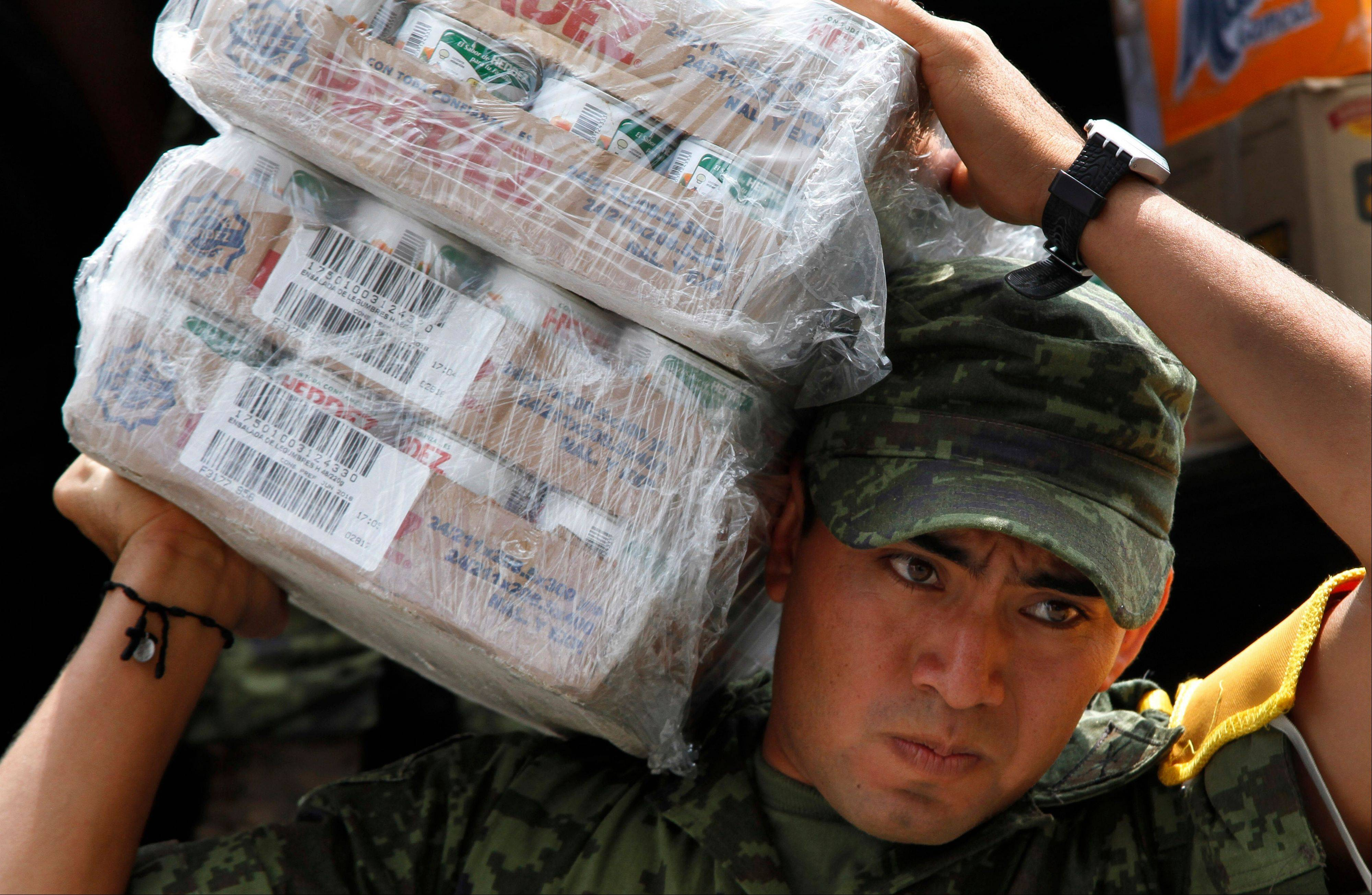 A soldier carries cartons of canned vegetables Friday to a waiting vehicle as part of the humanitarian aid bound for storm victims of Tropical Storm Manuel, in the Zocalo, Mexico City's main plaza.
