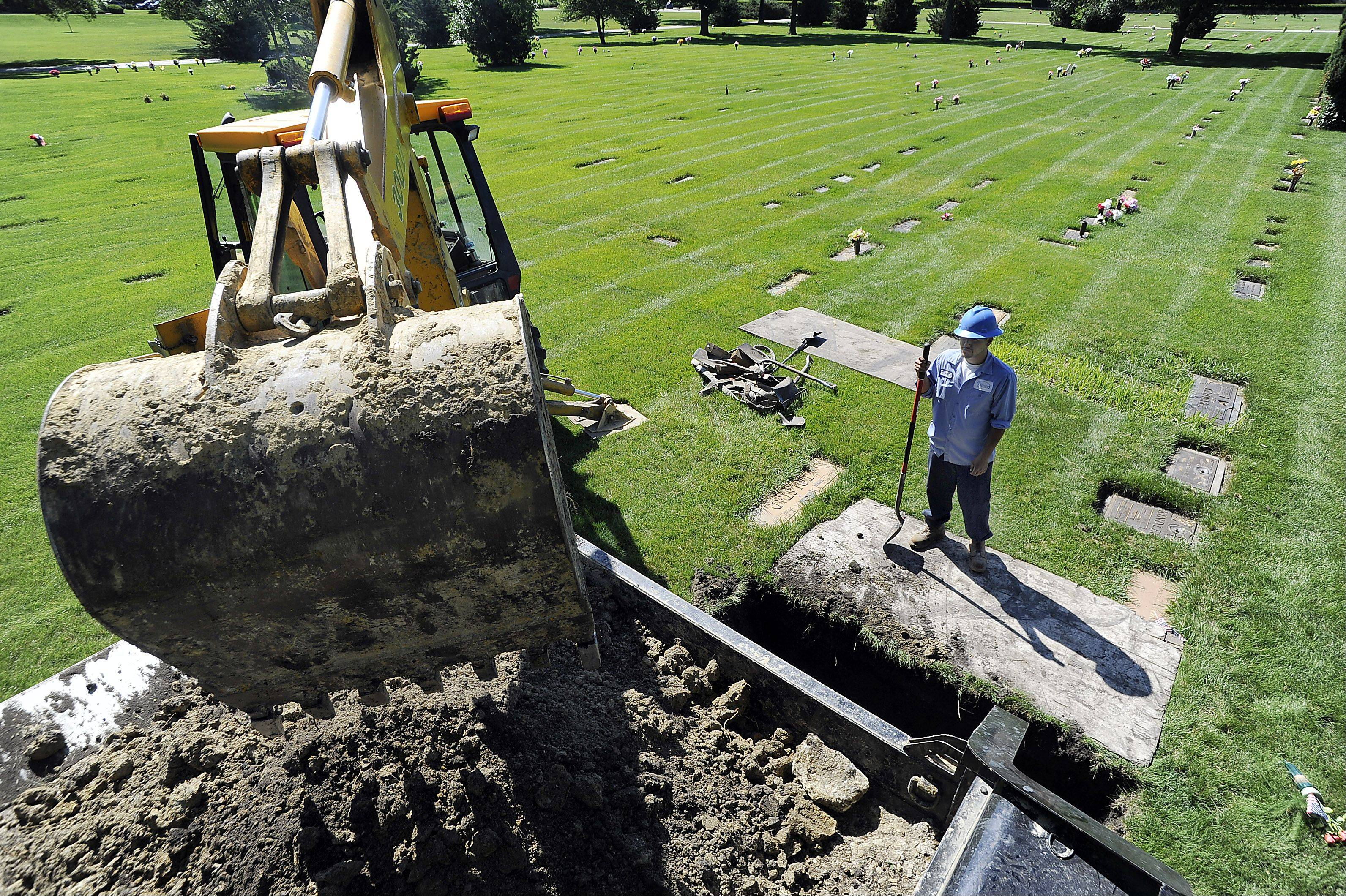 Adalberto Nevarez watches as the backhoe operator digs a grave at Memory Gardens Cemetery. He makes sure that it is deep enough to hold a vault.