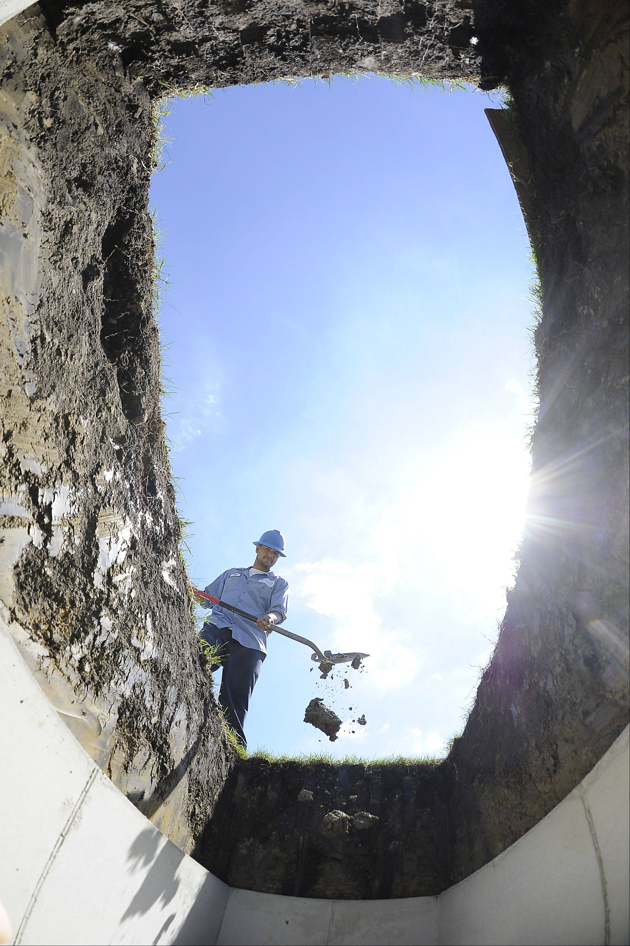 After the vault is lowered into a freshly dug grave, Adalberto Nevarez cleans up around the edges with a shovel, preparing it for the next day's service. Nevarez has dug thousands of graves in the four years he has worked at the cemetery.