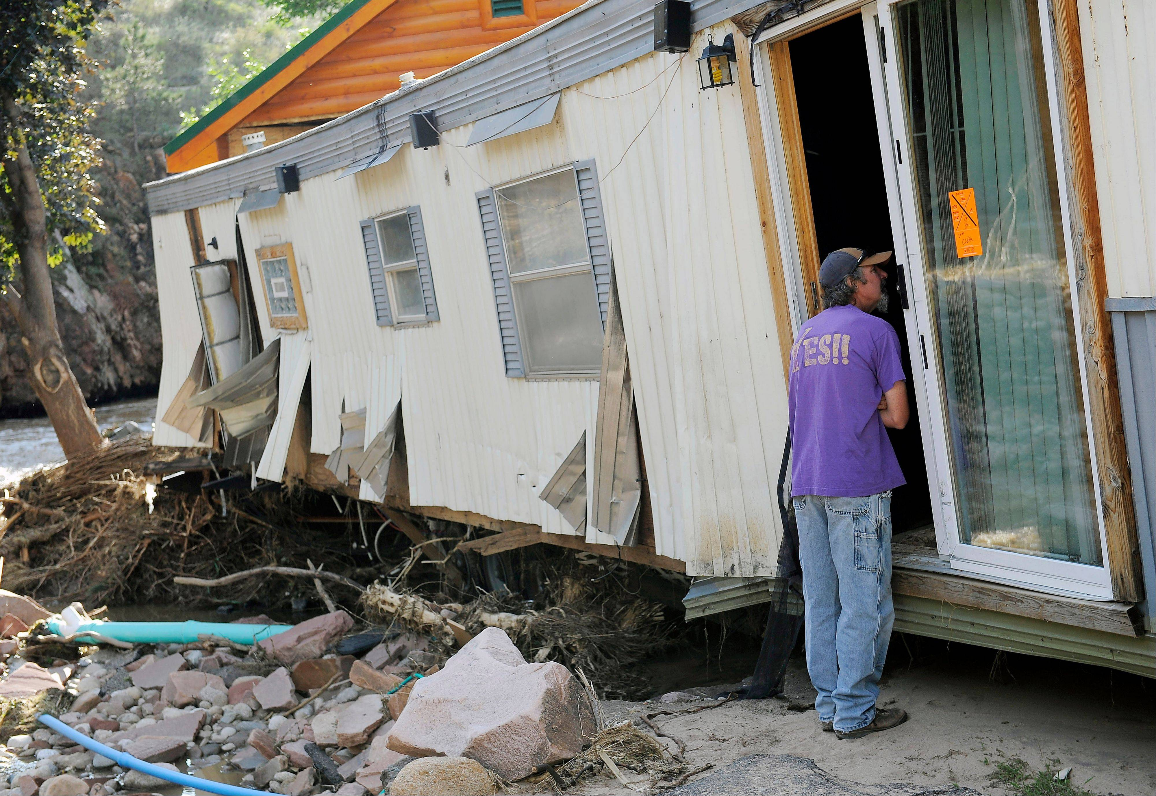 Dirk Huntington checks on a friend's flood-damaged trailer at the River Bend Mobile Home Park in Lyons, Colo., on Thursday, Sept. 19, 2013. Hundreds of evacuees were allowed past National Guard roadblocks Thursday to find a scene of tangled power lines, downed utility poles, and mud-caked homes and vehicles.
