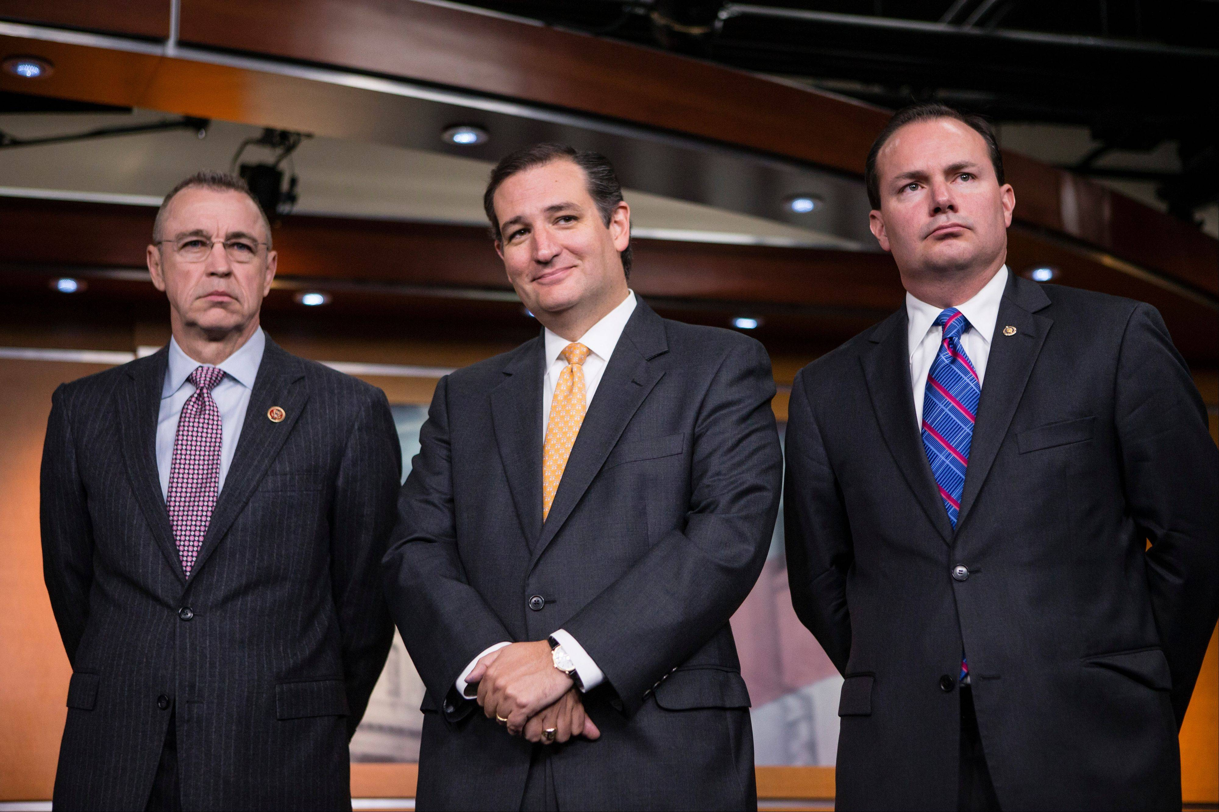 Sen. Ted Cruz, R-Texas, center, smiles during a news conference with conservative Congressional Republicans who persuaded the House leadership to include defunding the Affordable Care Act as part of legislation to prevent a government shutdown, at the Capitol in Washington, Thursday, Sept. 19, 2013. Sen. Cruz is flanked by Rep. Matt Salmon, R-Ariz., left, and Sen. Mike Lee, R-Utah, right.