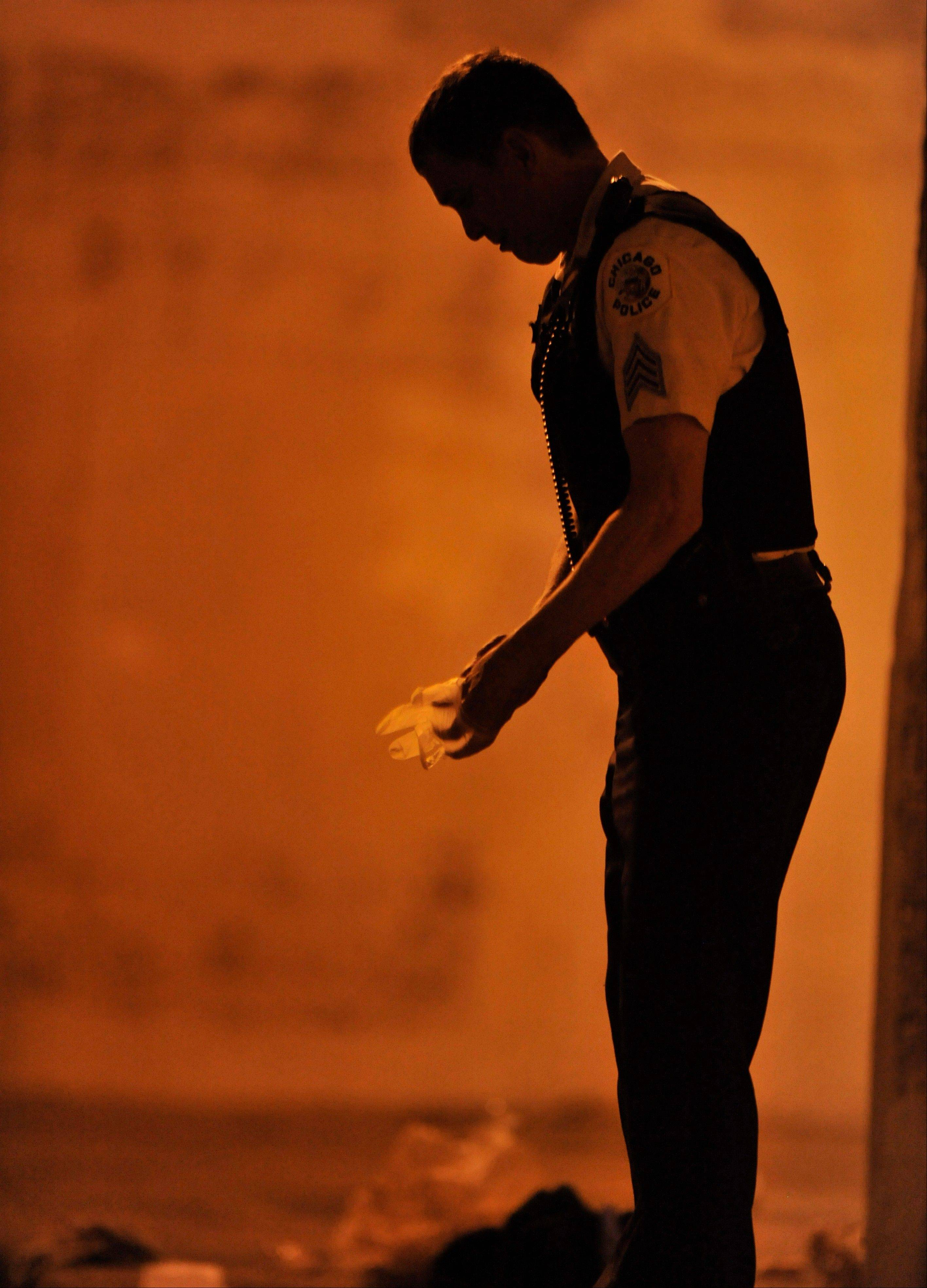A Chicago police detective investigates the scene where a number of people were shot Thursday in a Southwest Side park.