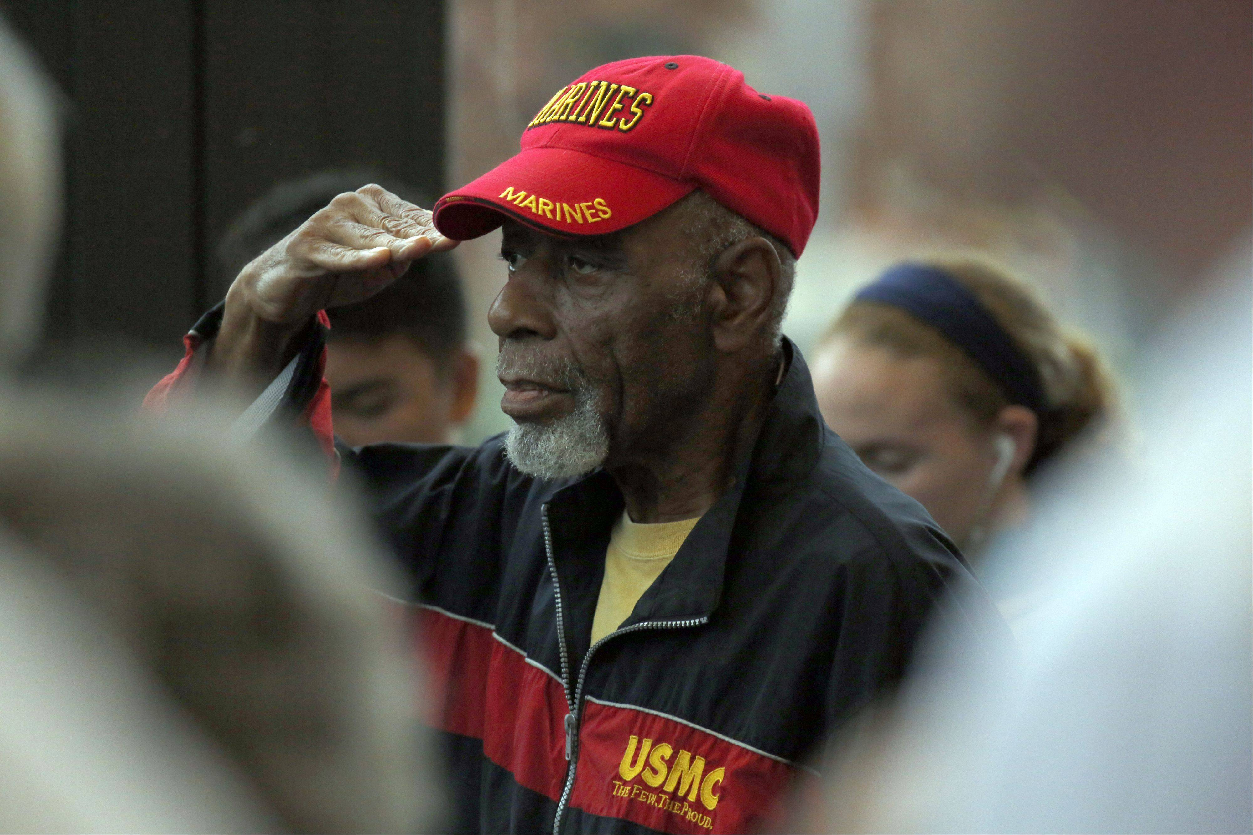 "Ernie Broadnax, who served in the Marines from 1955 to 1966, salutes as the colors are presented during the opening ceremony for ""The Wall That Heals"" at The Hemmens Cultural Center in Elgin yesterday."