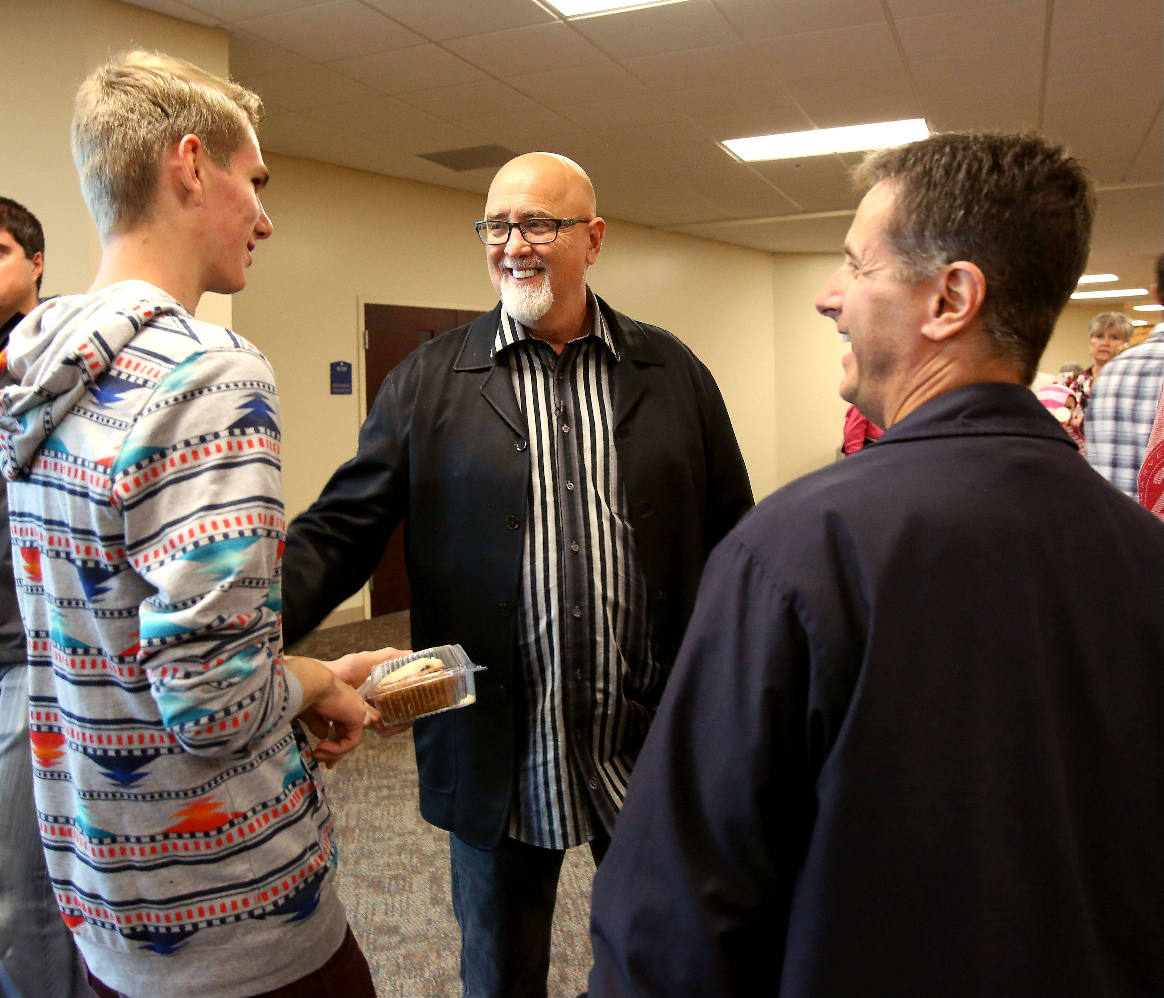 Pastor James MacDonald, center, welcomes Bob Heck of Algonquin and his son Tyler, 16, left, to the Harvest Bible Chapel in Elgin.