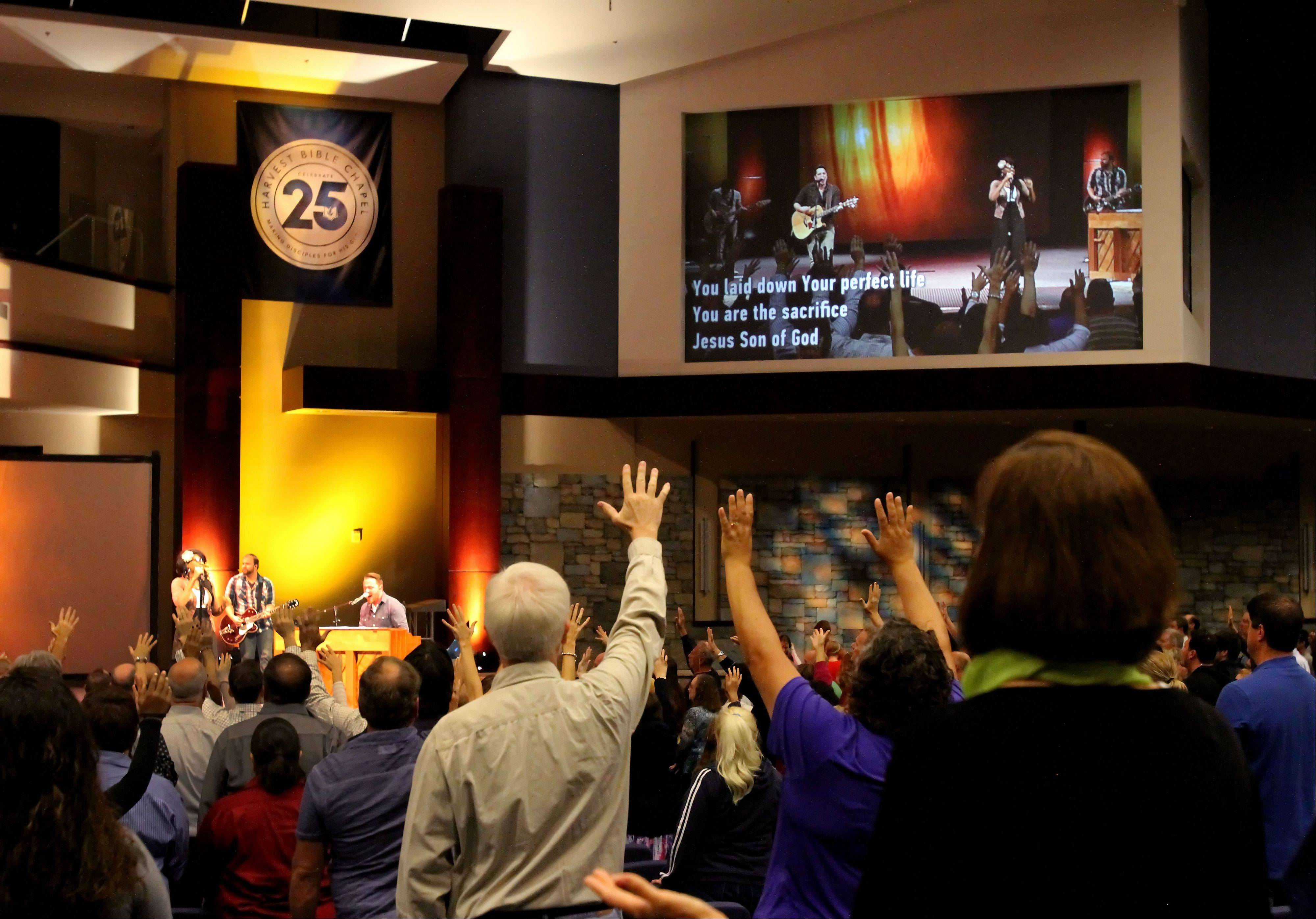 Pastor James MacDonald, top, speaks at the pulpit in the Elgin branch of Harvest Bible Church, which also hosted the Vertical Church Band, above, at a recent Sunday service. MacDonald speaks from a different Harvest Bible house of worship each week, while his message is beamed to the other churches.