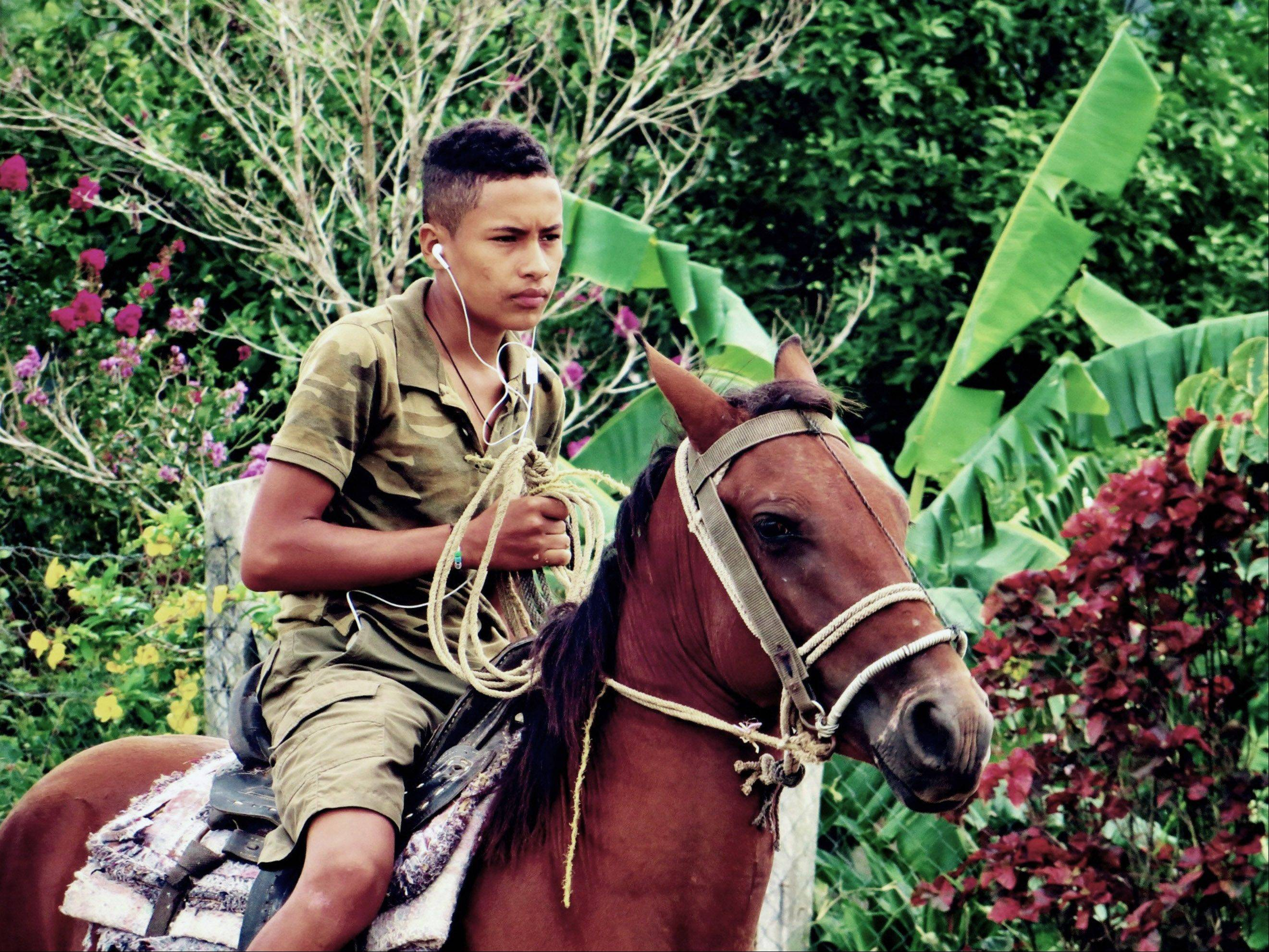 A Honduran rancher's son rounds up horses in a primitive fashion while listening to his iPod in San Esteban, Honduras on August 3.