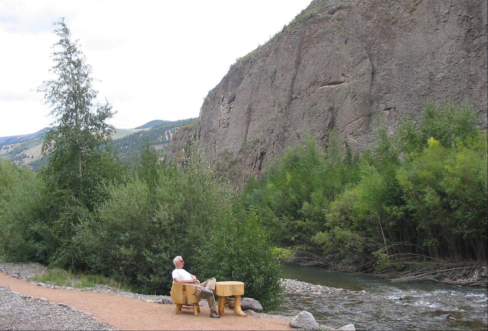 A self-portrait by Steve Parmelee as he sits at a hand-carved table and chair alongside a stream near Lake City, Colorado on September 3, 2005.