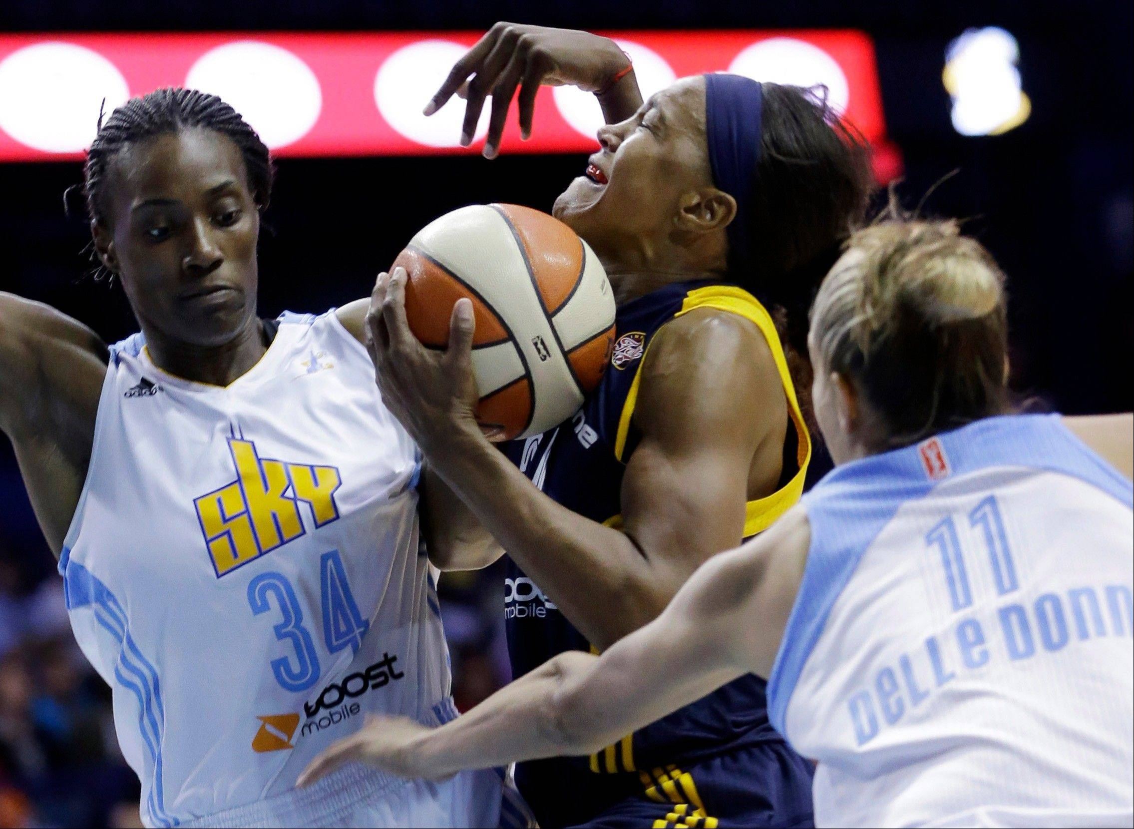 Indiana Fever forward Tamika Catchings, center, drives to the basket between Chicago Sky center Sylvia Fowles, left, and forward Elena Delle Donne during the first half in Game 1 of the WNBA basketball Eastern Conference semifinal series on Friday, Sept. 20, 2013, in Rosemont, Ill.