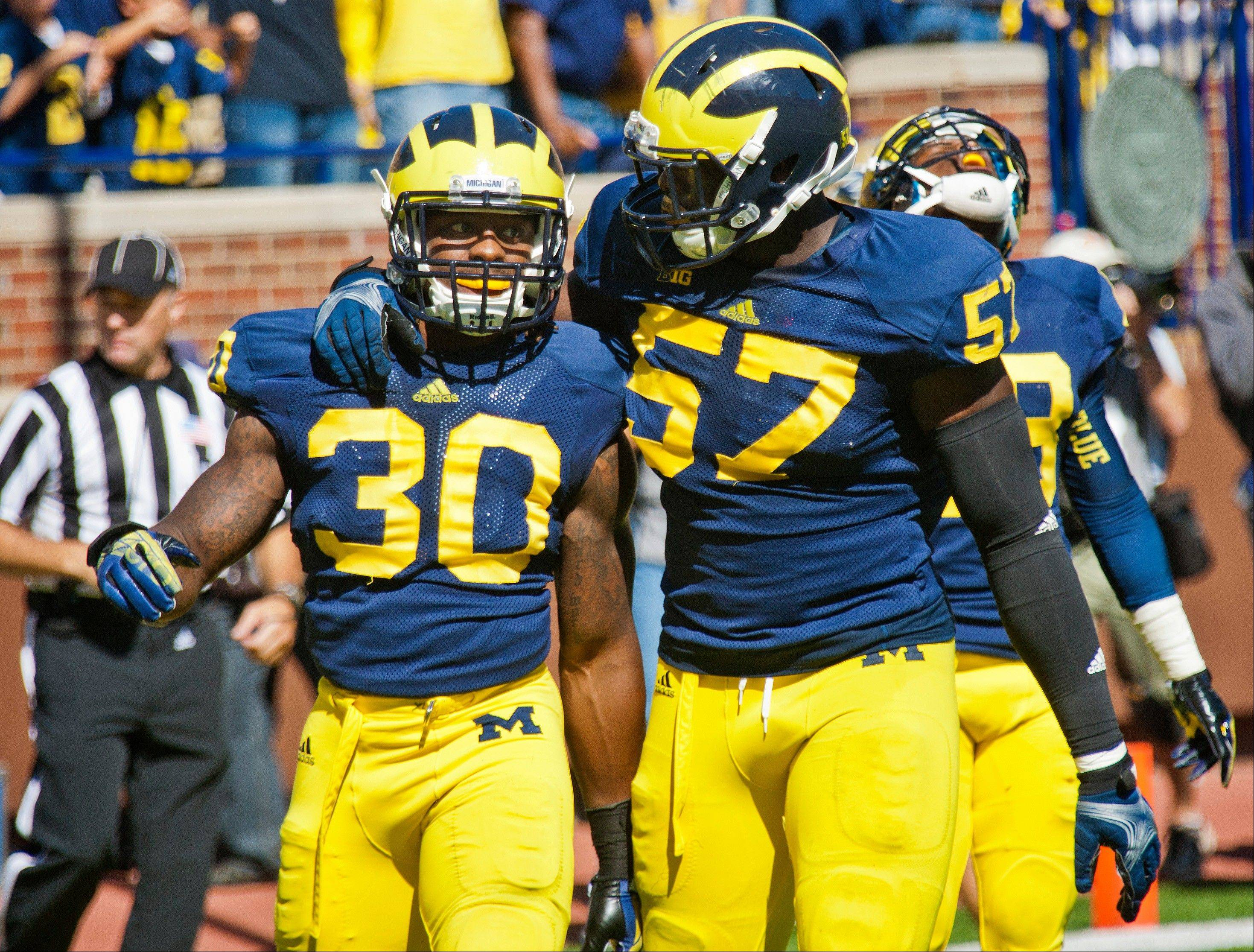 Michigan safety Thomas Gordon (30) and offensive lineman Patrick Kugler (57) celebrate after stopping Akron from scoring in the final seconds of last Saturday's game in Ann Arbor, Mich.
