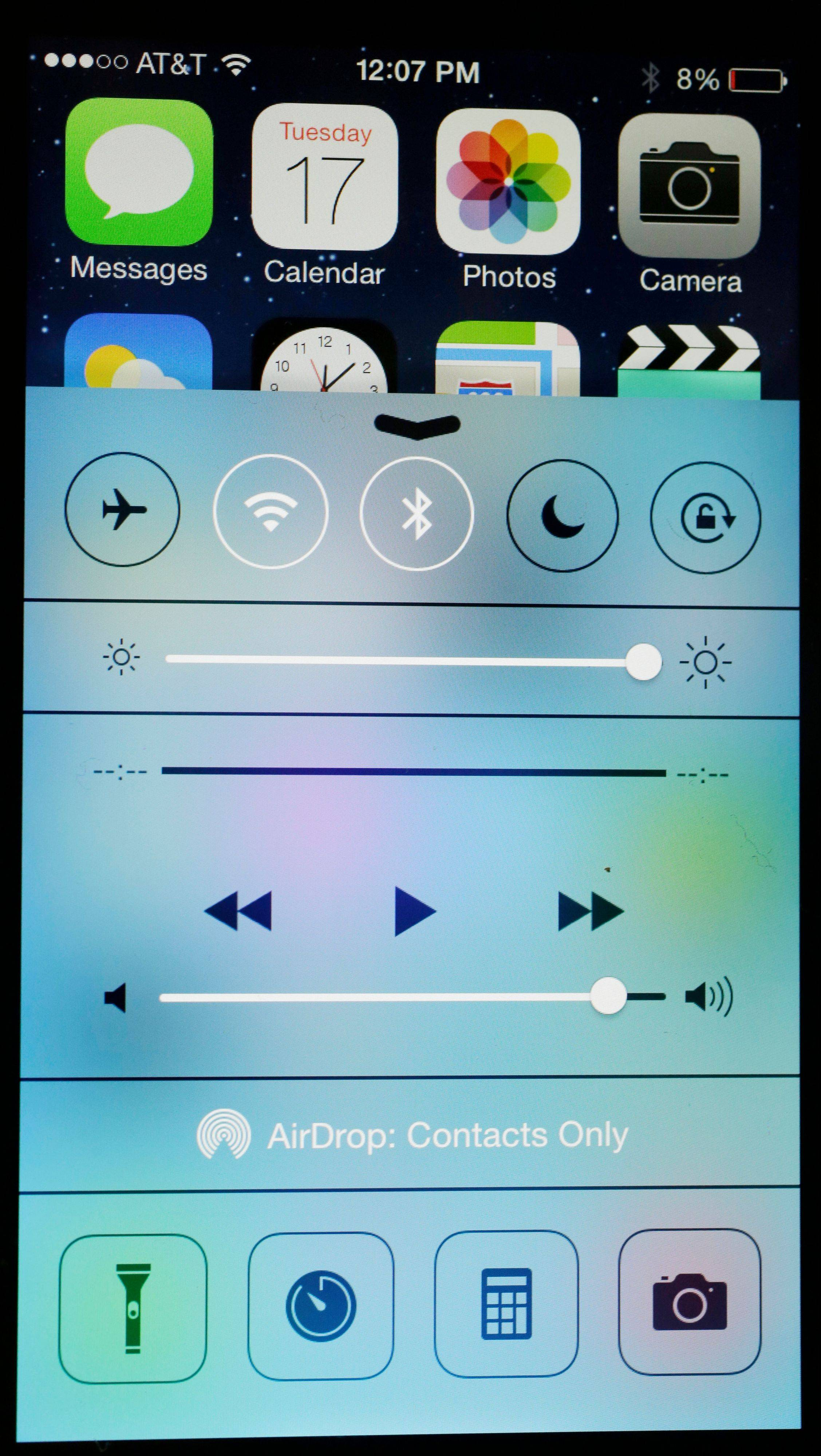 An iPhone with iOS 7 software displays the new look of the Control Center in New York. Much of the new iOS 7 software is about cosmetic changes.