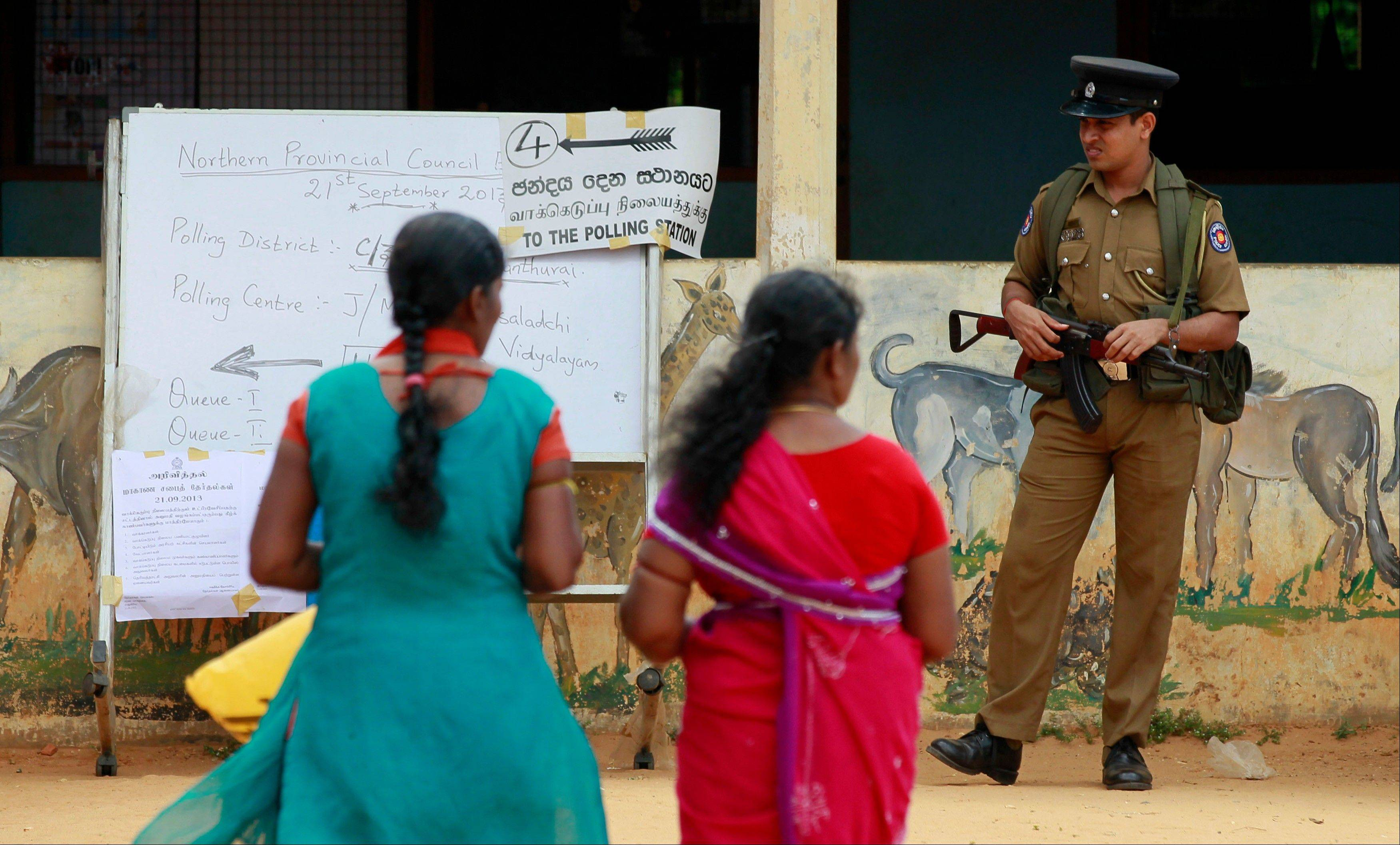 A Sri Lankan police officer stands guard as ethnic Tamils women arrive to cast their vote at a polling station during the northern provincial council election in Jaffna, Sri Lanka, Saturday, Sept. 21. Ethnic Tamil voters in Sri Lanka�s war-ravaged north went to the polls Saturday to form their first functioning provincial government, hoping it is the first step toward wider regional autonomy after decades of peaceful struggle and a bloody civil war.