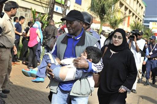 A rescue worker helps a child outside the Westgate Mall in Nairobi, Kenya Saturday, Sept. 21, 2013, after gunmen threw grenades and opened fire during an attack that left multiple dead and dozens wounded. A witness to the attacks on the upscale shopping mall says that gunmen told Muslims to stand up and leave and that non-Muslims would be targeted. (AP Photo/Riccardo Gangale)