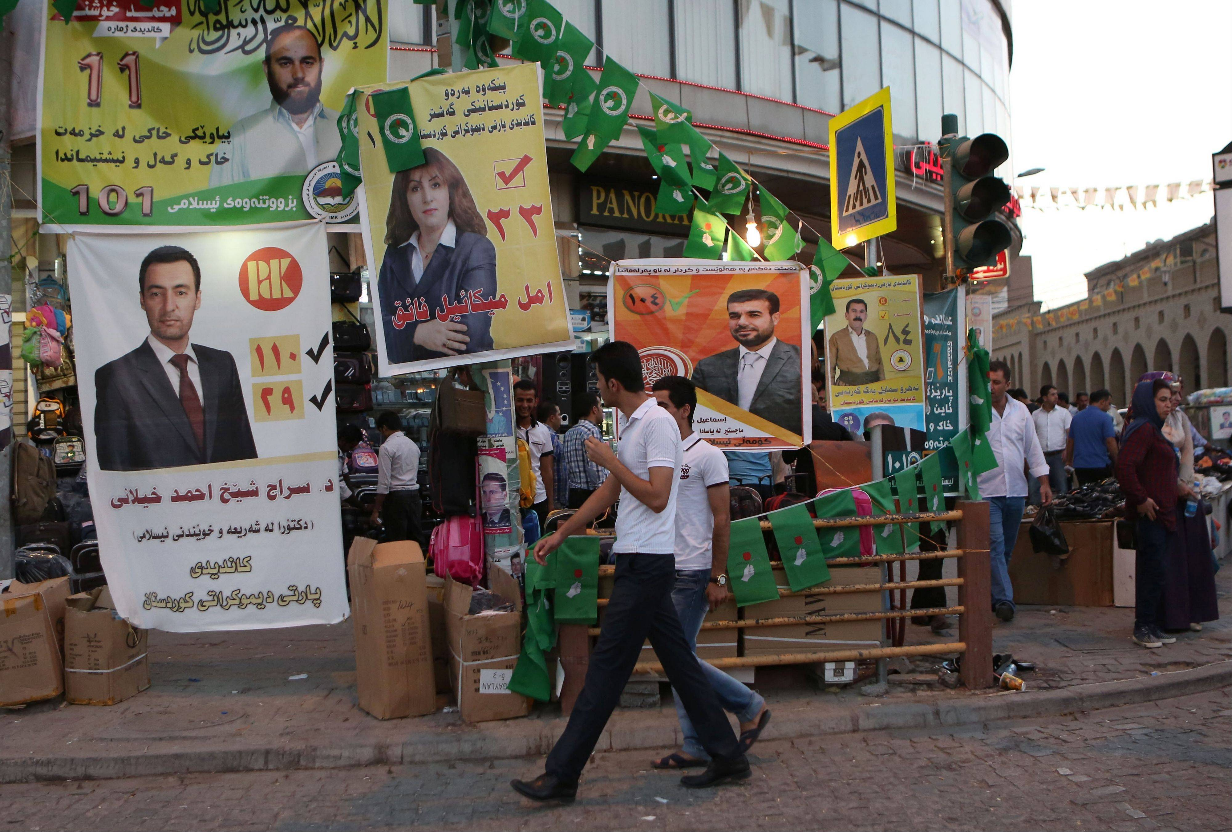 People walk past election campaign posters Friday of different parties, in Irbil, Iraq, a day ahead of the self-ruled northern Kurdish region�s fourth election for local parliament since 1992.
