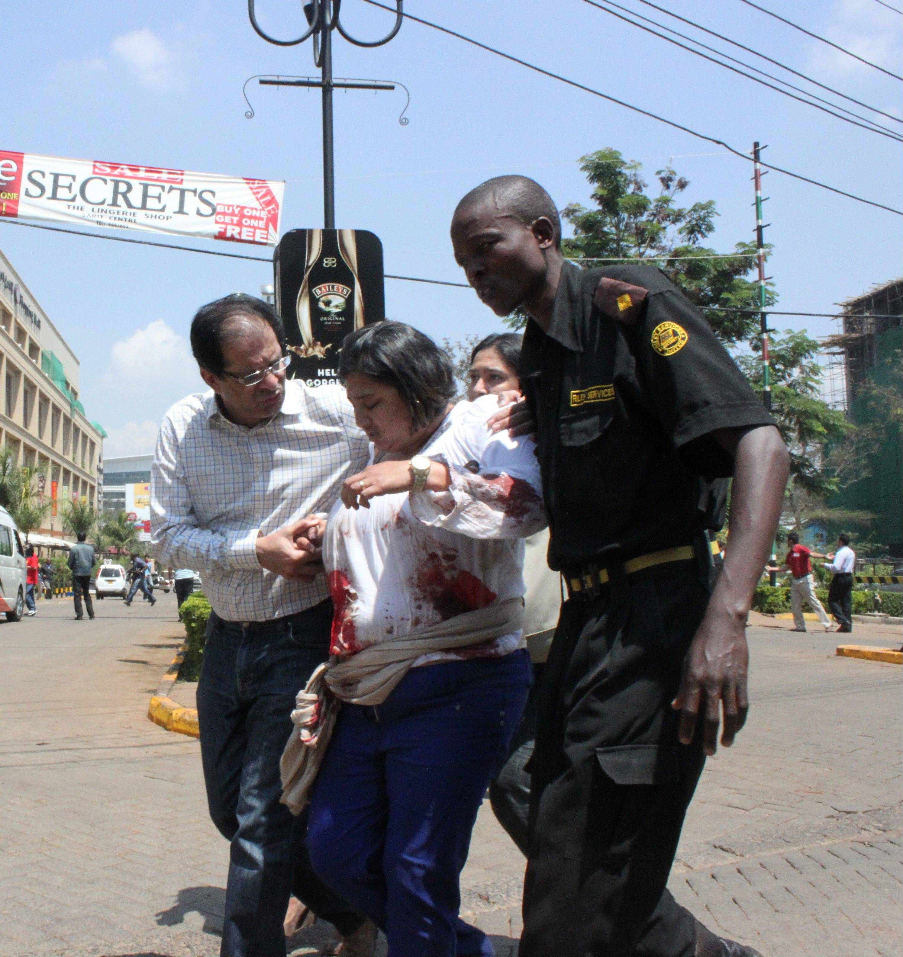 A security officer helps a wounded woman outside the Westgate Mall in Nairobi, Kenya on Saturday, Sept. 21, after gunmen threw grenades and opened fire during an attack that left multiple dead bodies and dozens wounded. A witness to the attacks on the upscale shopping mall says that gunmen told Muslims to stand up and leave and that non-Muslims would be targeted.